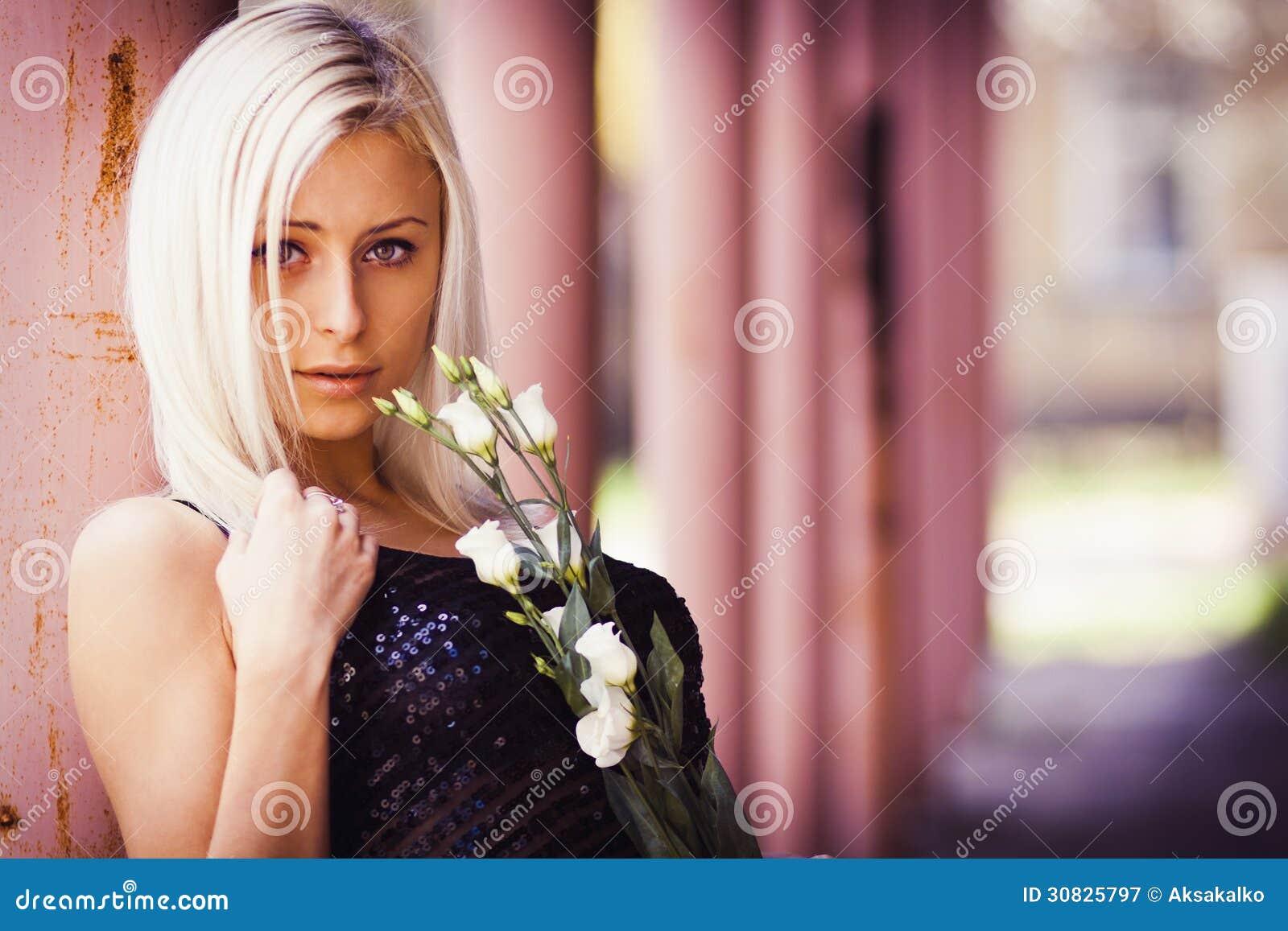 Bella ragazza bionda con la rosa di bianco