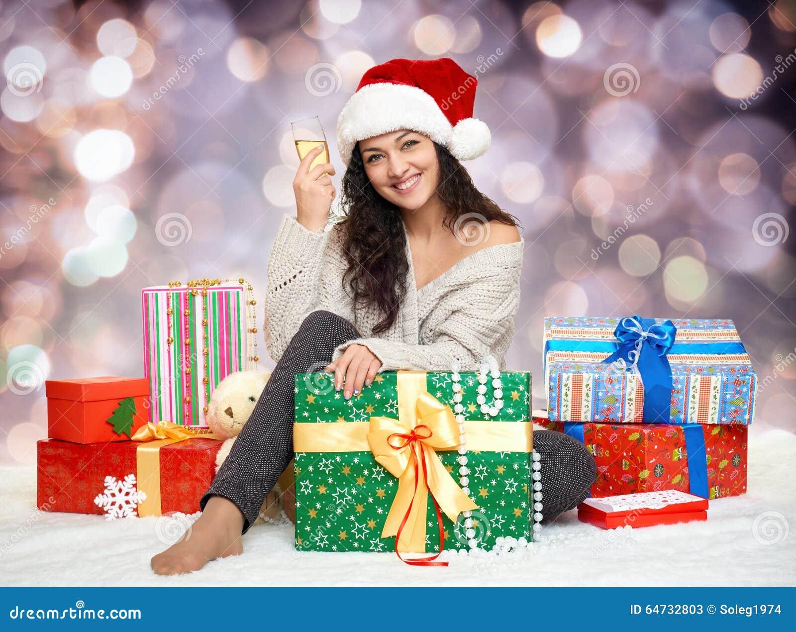 Bella ragazza in cappello di Santa con vetro dei contenitori di regalo e di champagne