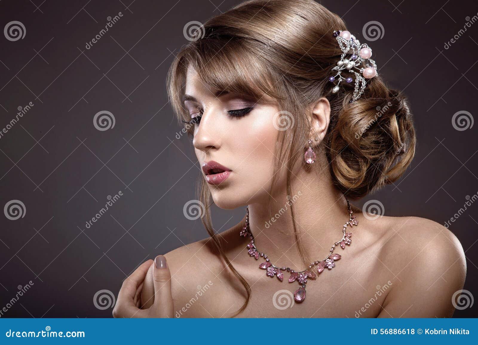 Bella ragazza castana con trucco di sera e pelle perfetta