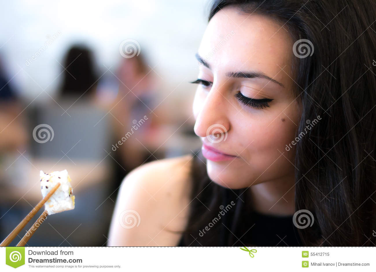 Bella ragazza che guarda e che mangia i sushi