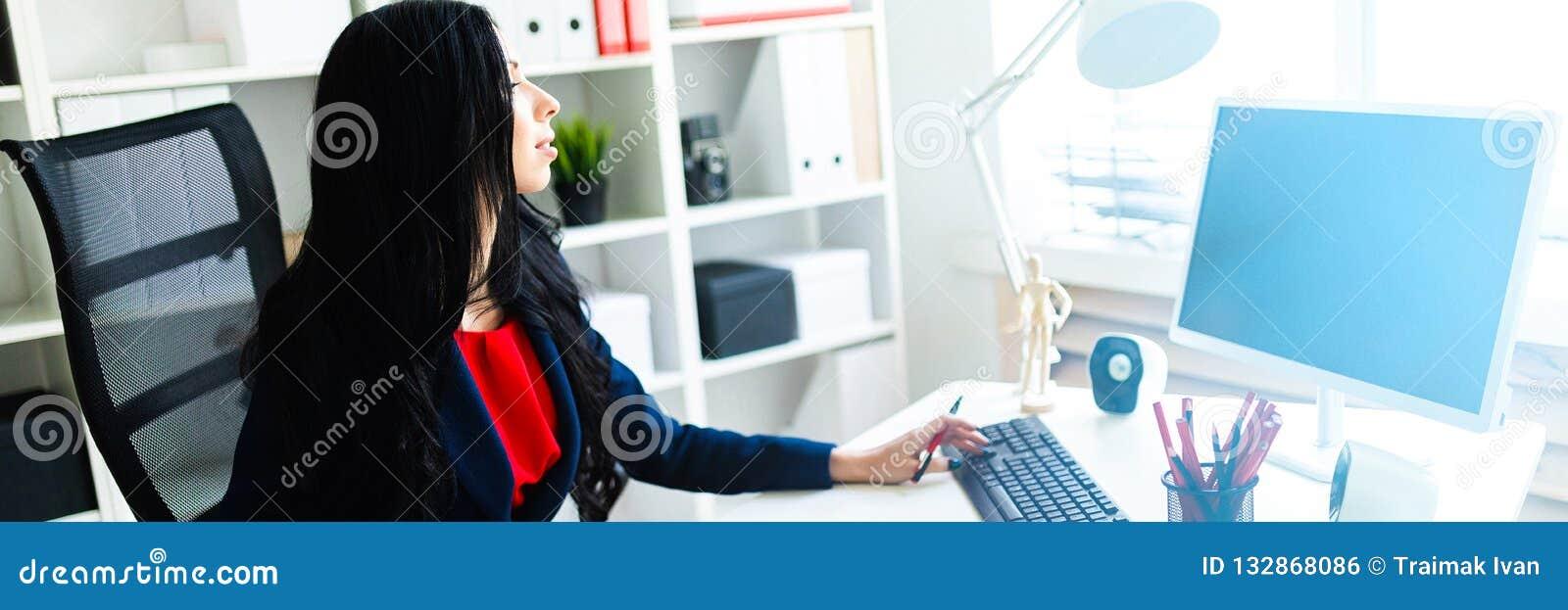 Bella ragazza che lavora con il computer ed i documenti nell ufficio alla tavola