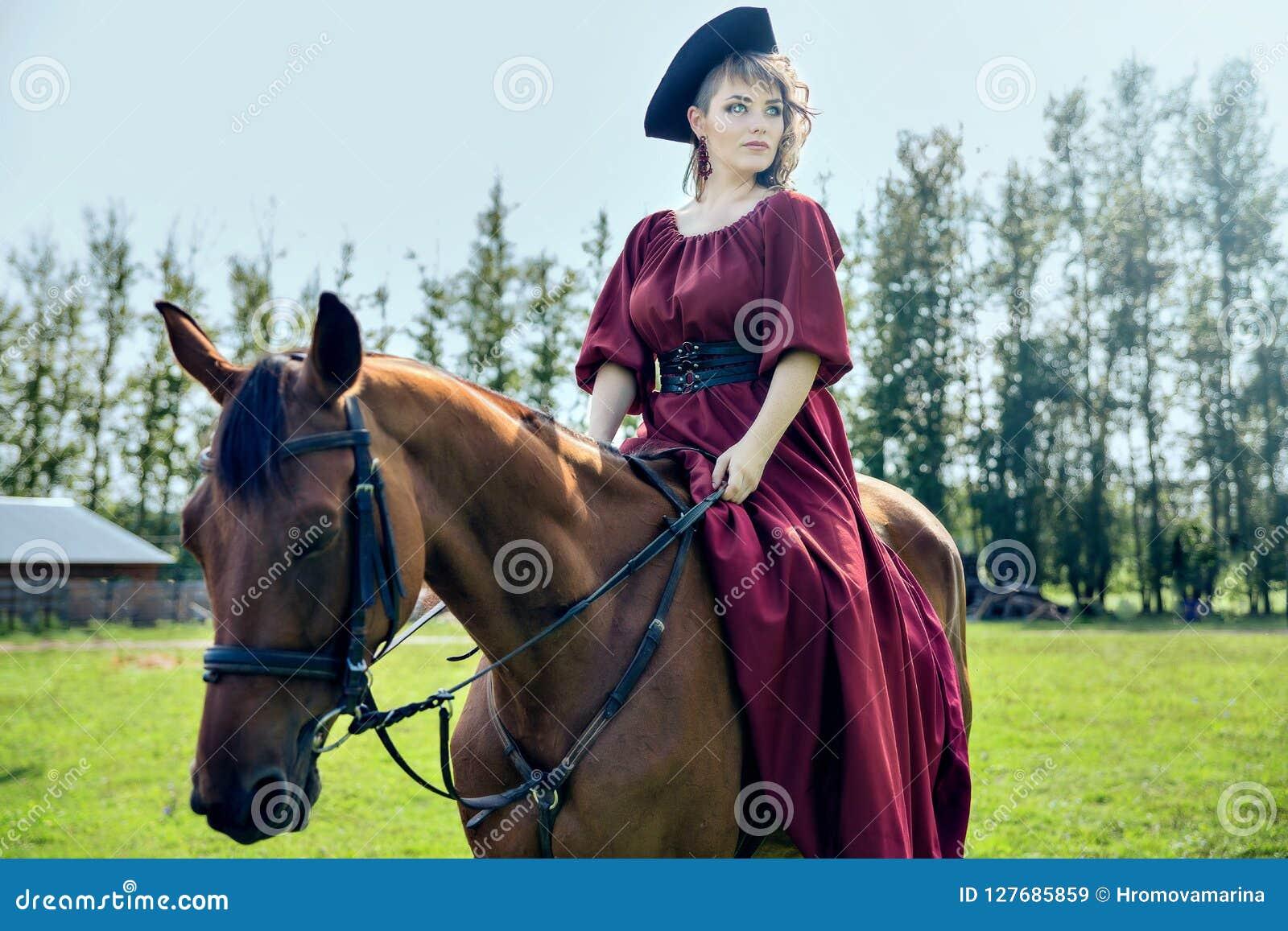 Bella ragazza che monta un cavallo marrone