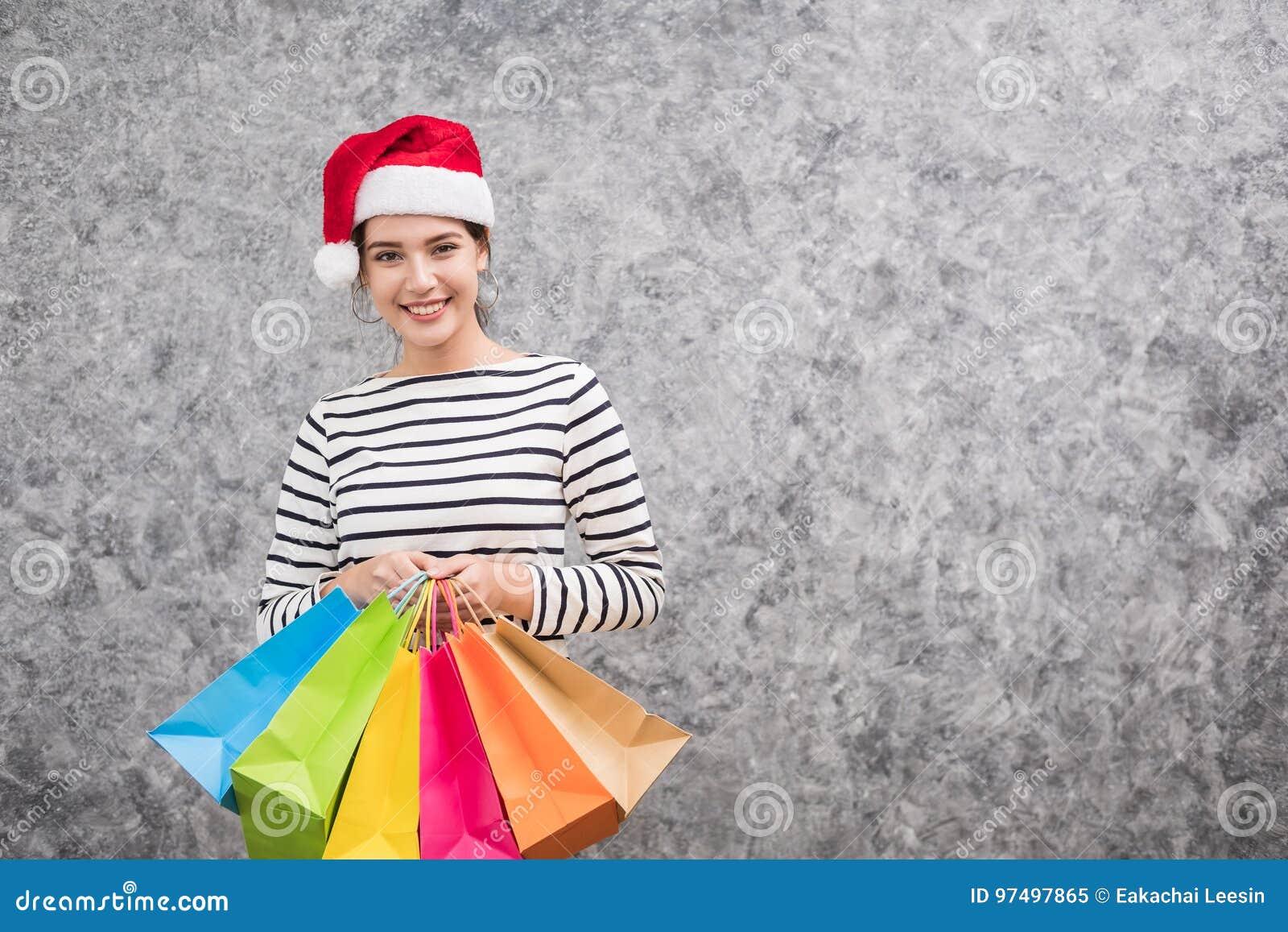 Bella ragazza che porta un cappello di Santa che tiene i lotti dei sacchetti della spesa