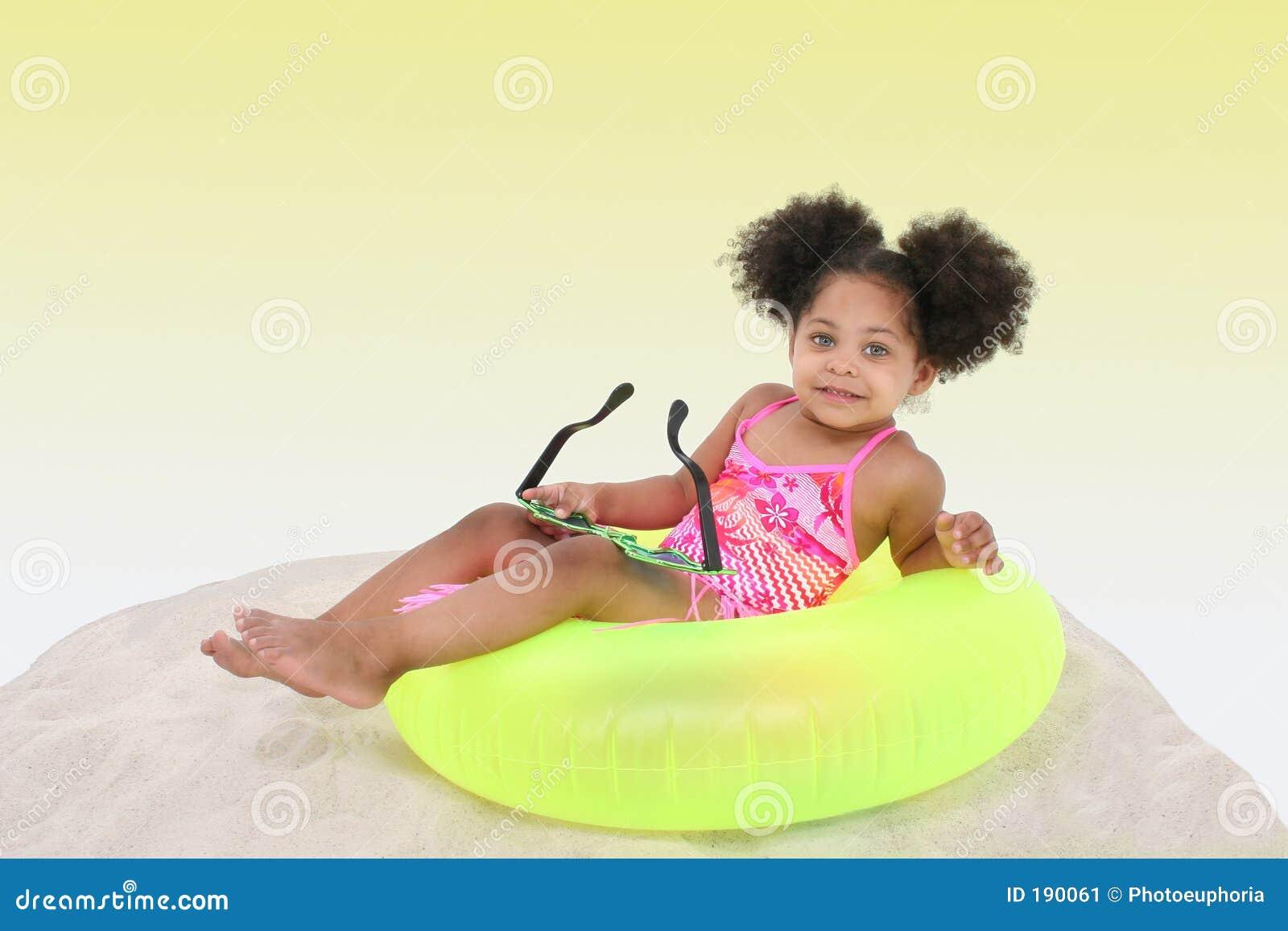 Bella ragazza che risiede nella sabbia su Floaty