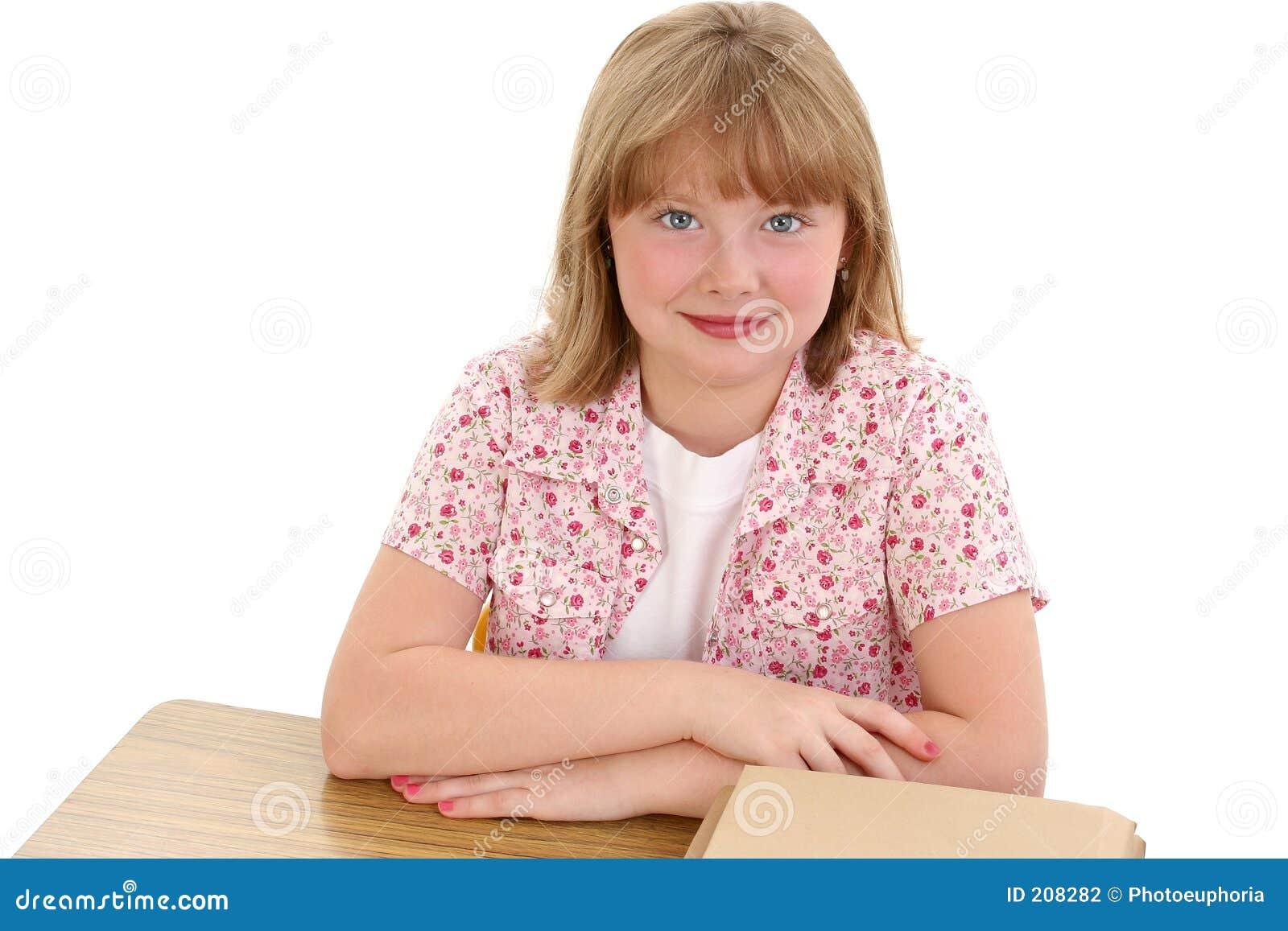 Bella ragazza che si siede allo scrittorio del banco