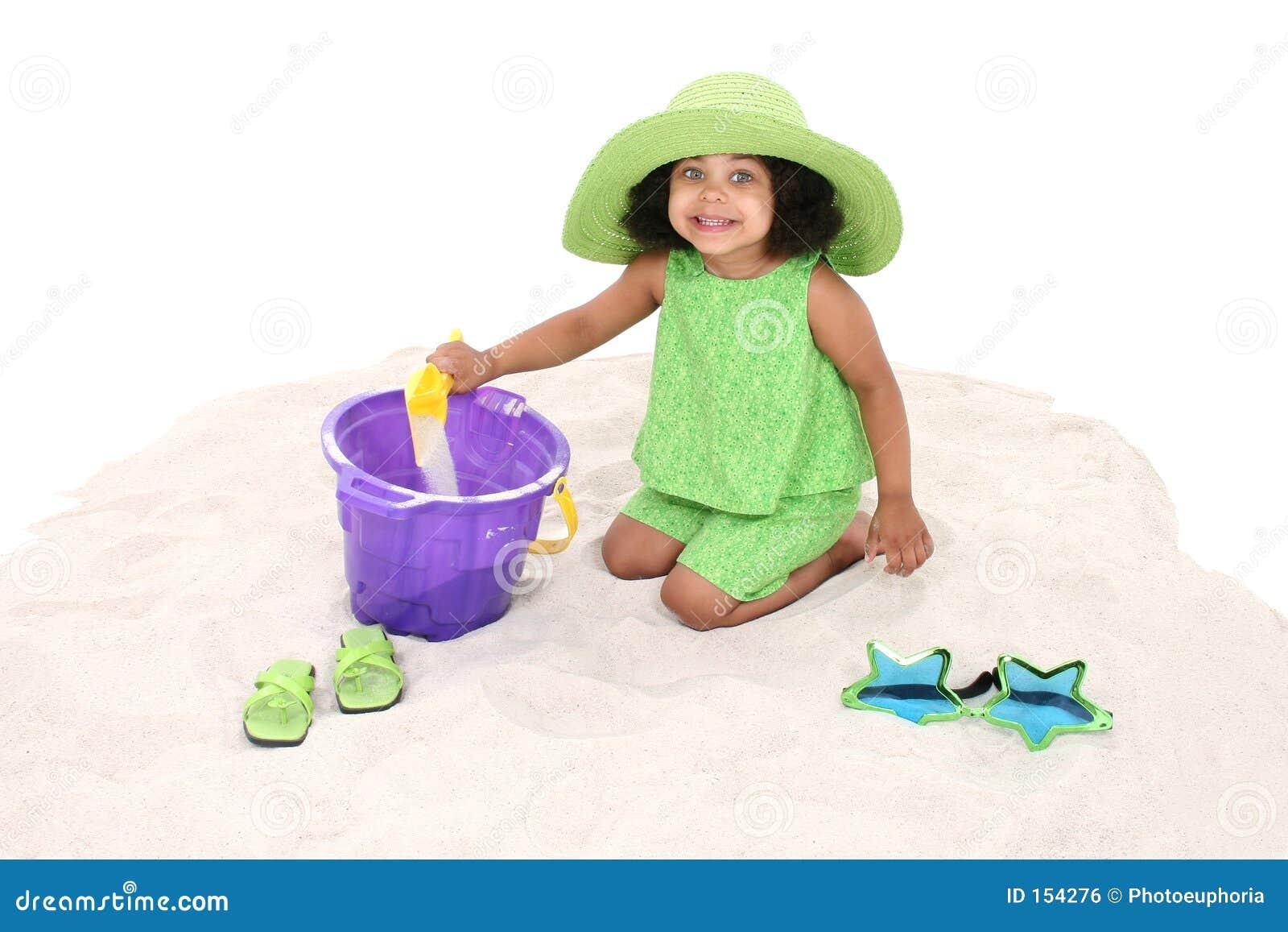 Bella ragazza che si siede nel gioco della sabbia