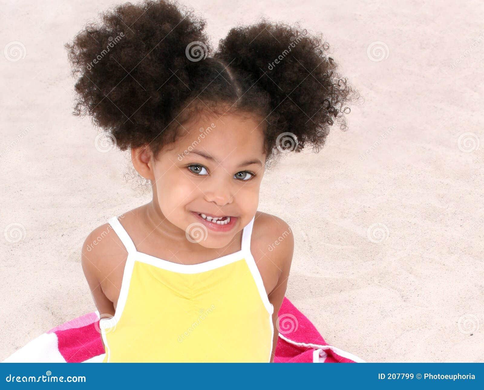 Bella ragazza che si siede sul tovagliolo di spiaggia nella sabbia
