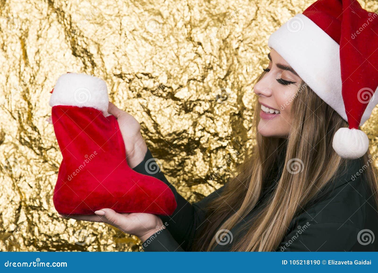 Bella ragazza con capelli lunghi in un cappello di Santa Claus con lo  stivale di lana rosso per i regali in mani su un fondo dell oro 39a6442dfe2e