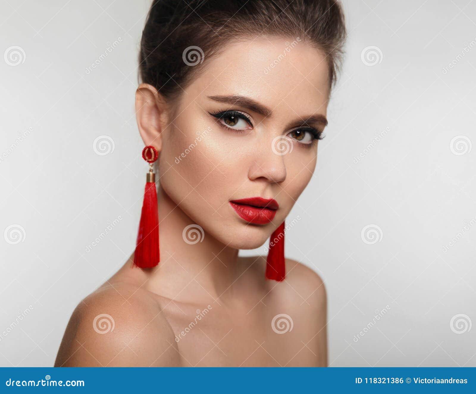 Bella ragazza con i gioielli degli orecchini Fronte di bellezza di giovane brune