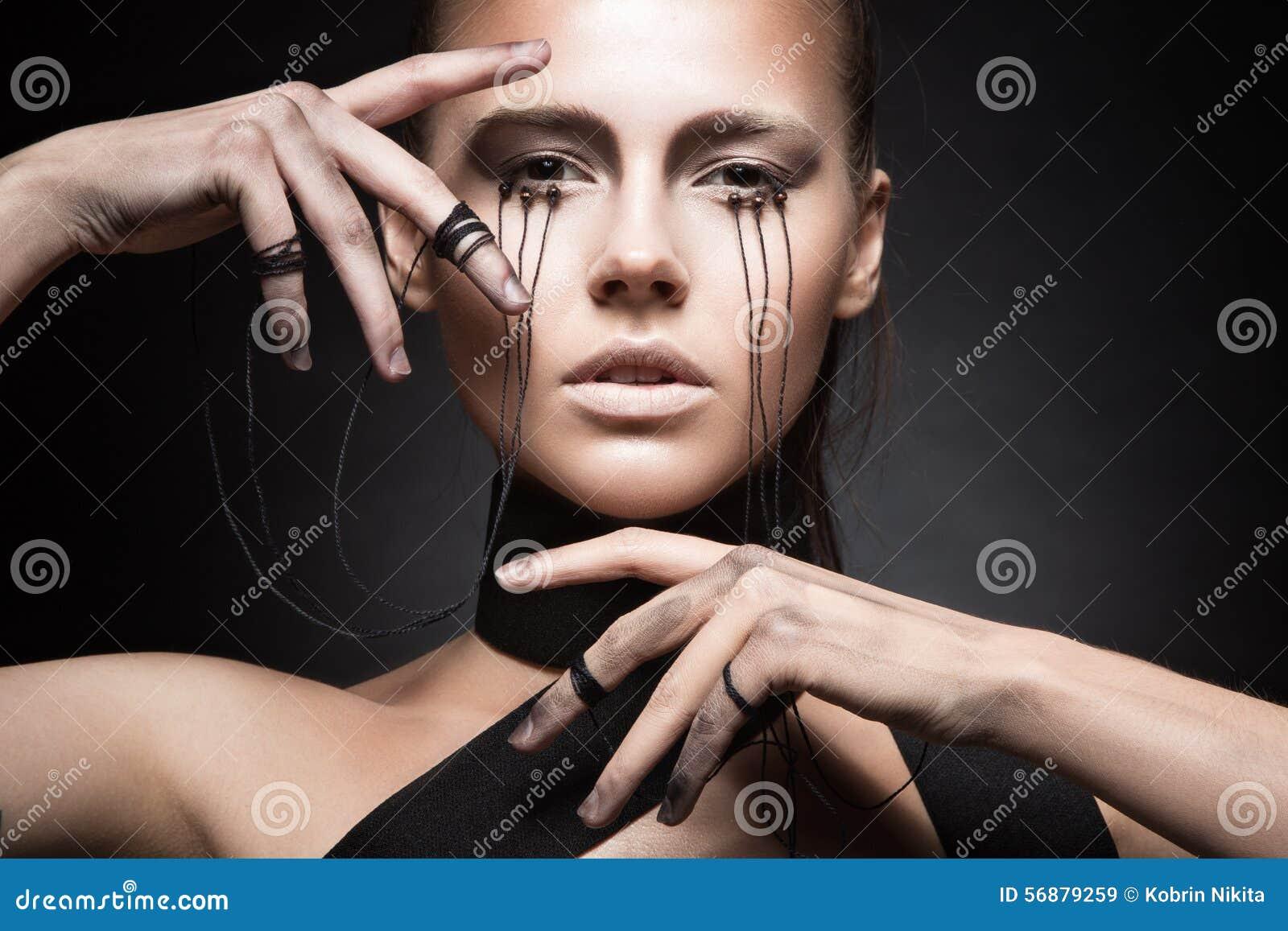 Bella ragazza con trucco creativo nello stile gotico ed i fili degli occhi Fronte di bellezza di arte