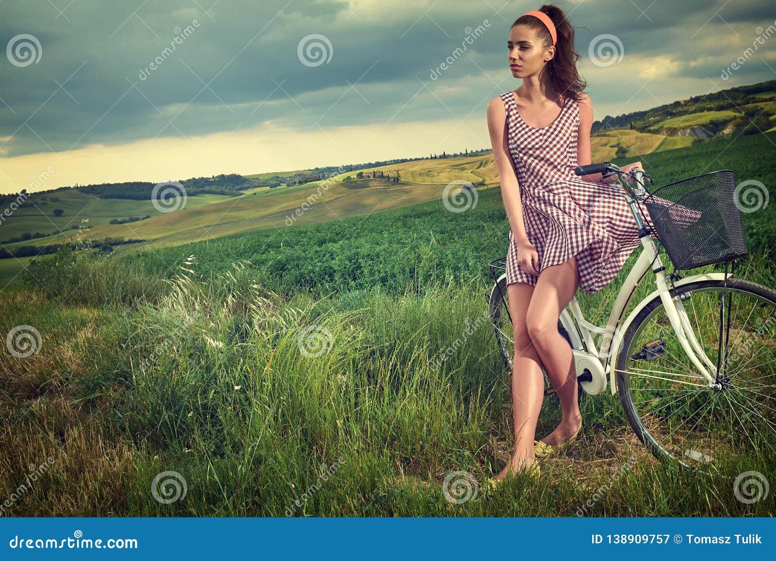 Bella ragazza d annata che si siede accanto alla bici, ora legale