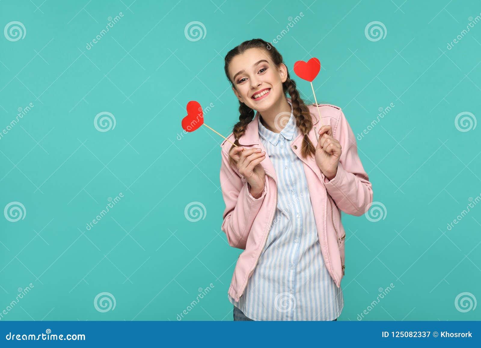 Bella ragazza felice nello stile casuale, nell acconciatura della treccia e nel rosa