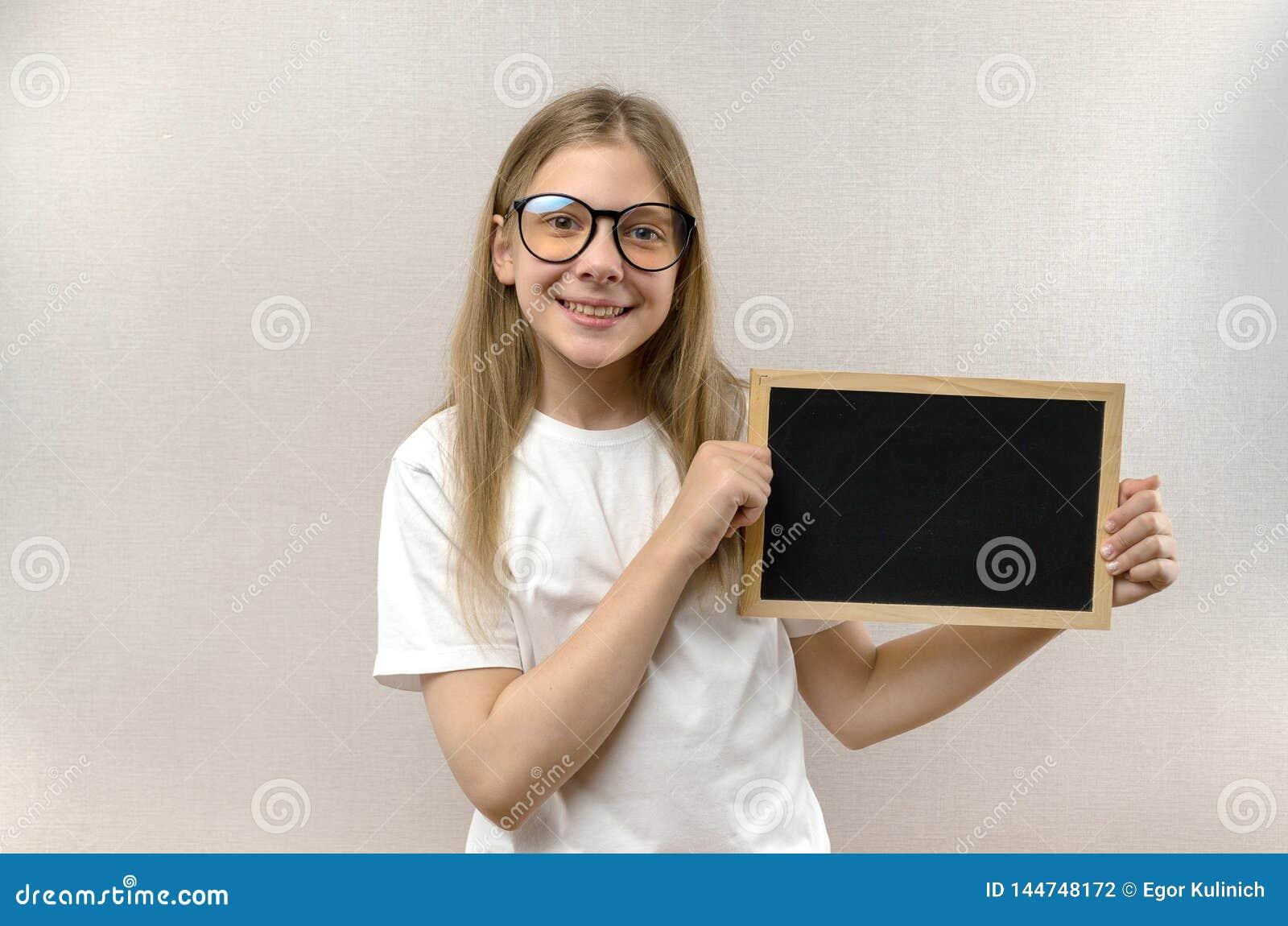 Bella ragazza maligna con i vetri che tengono un segno dentro le sue mani Copia-spazio