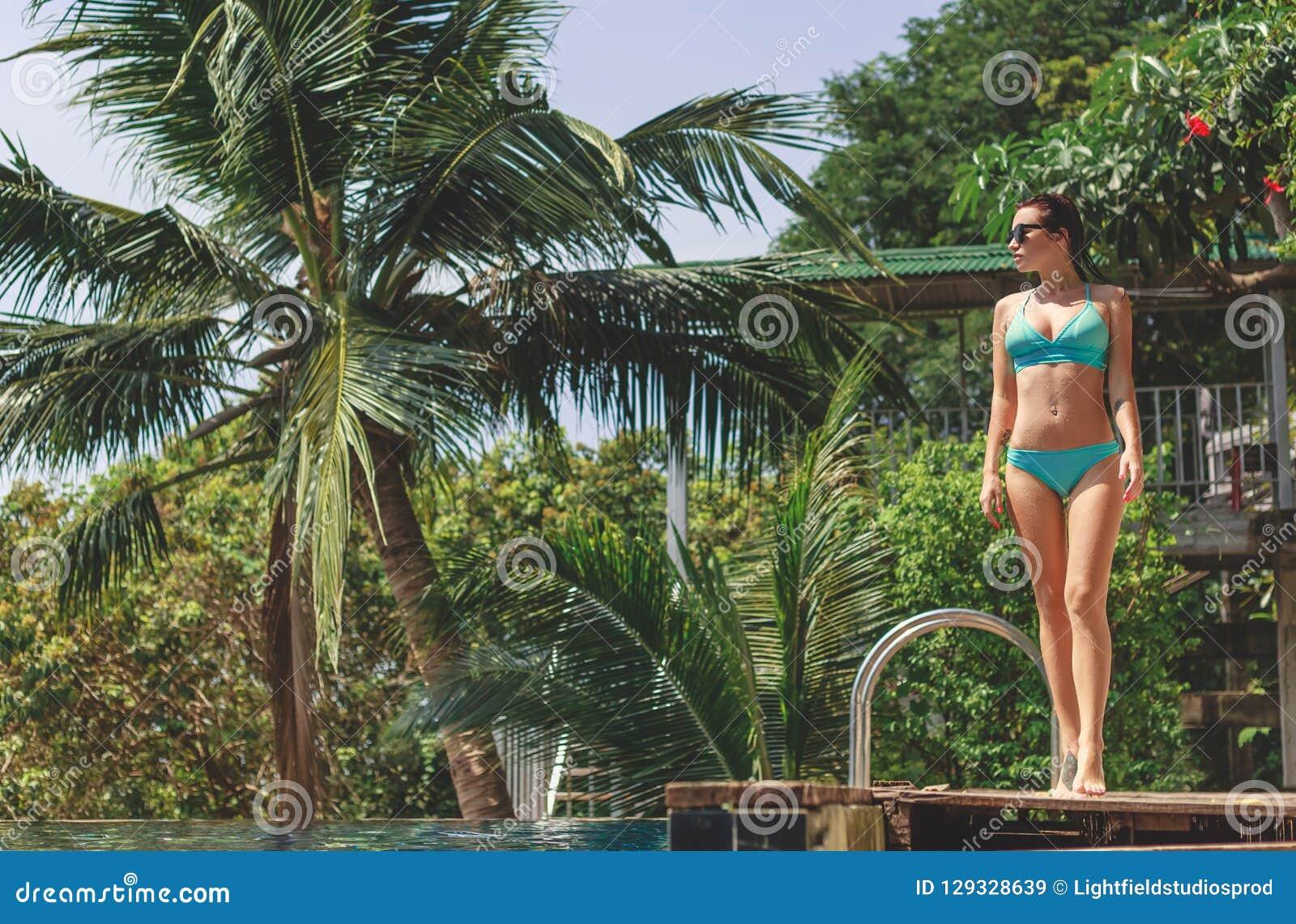 Bella ragazza nella condizione del bikini vicino alla piscina