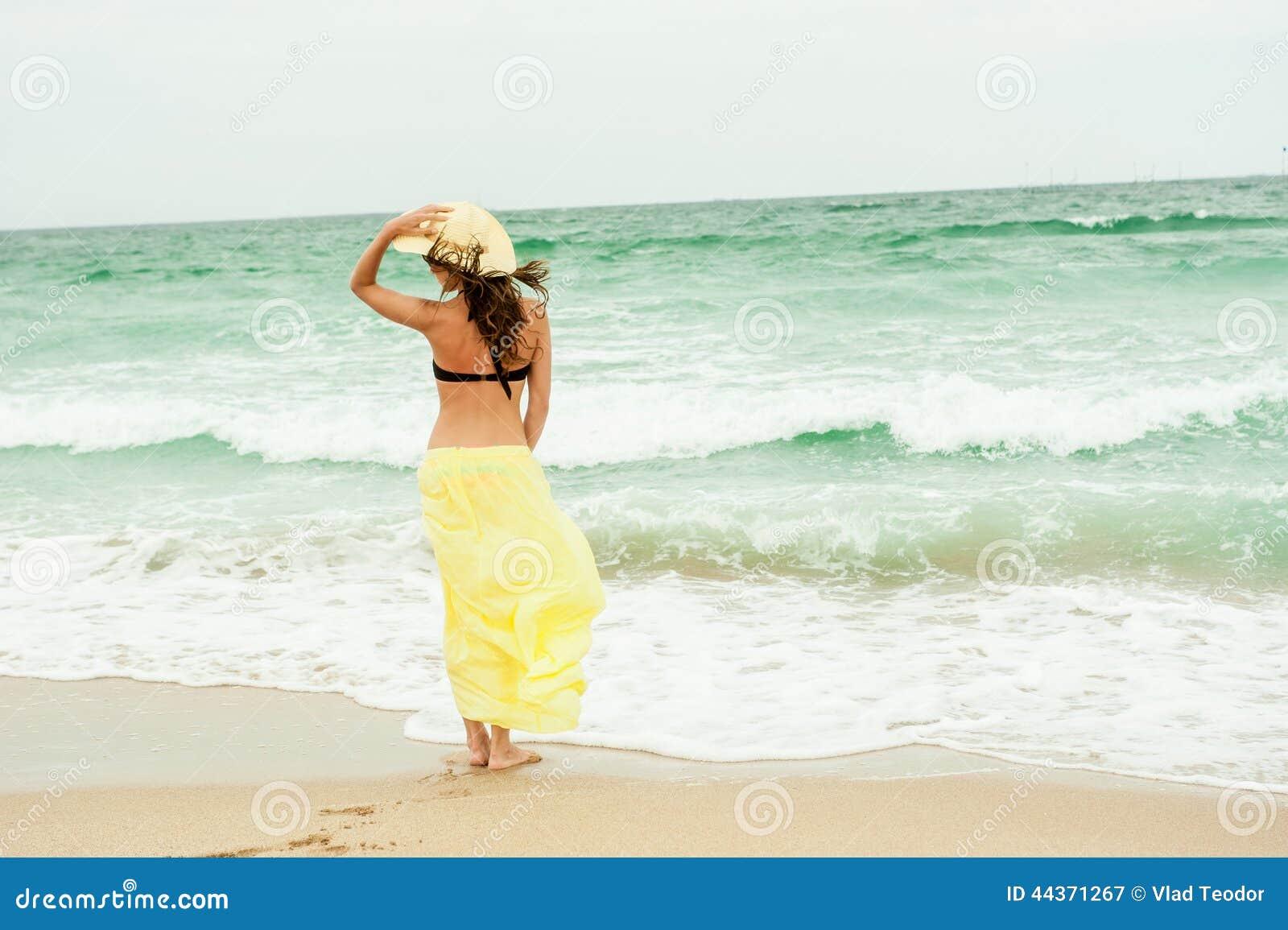 Bella ragazza nella spiaggia gialla dell acqua del vestito