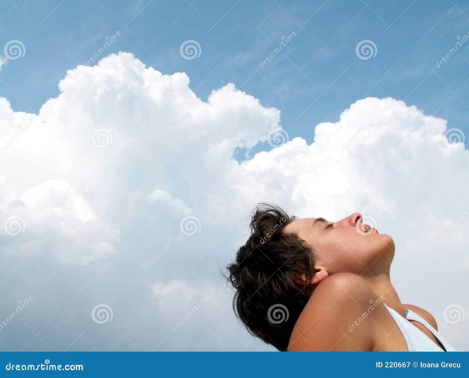 Bella ragazza profilata sui cieli nuvolosi
