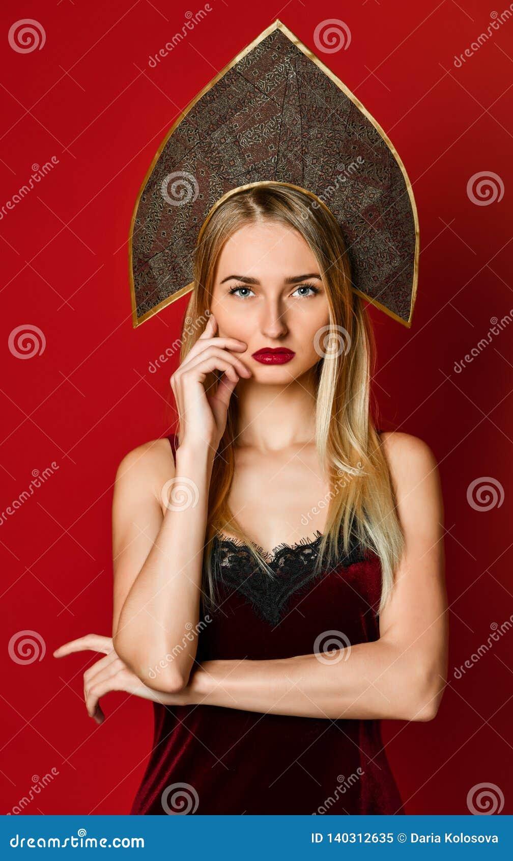 Bella ragazza russa bionda sexy in cappello tradizionale del kokoshnik, vestito festivo dal velluto su un fondo rosso,