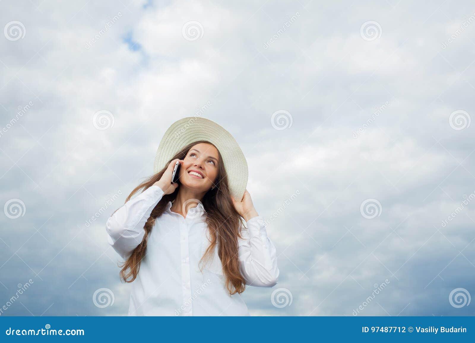 Bella ragazza sorridente in un cappello bianco con un ampio bordo che parla sul telefono su fondo delle nuvole di tempesta