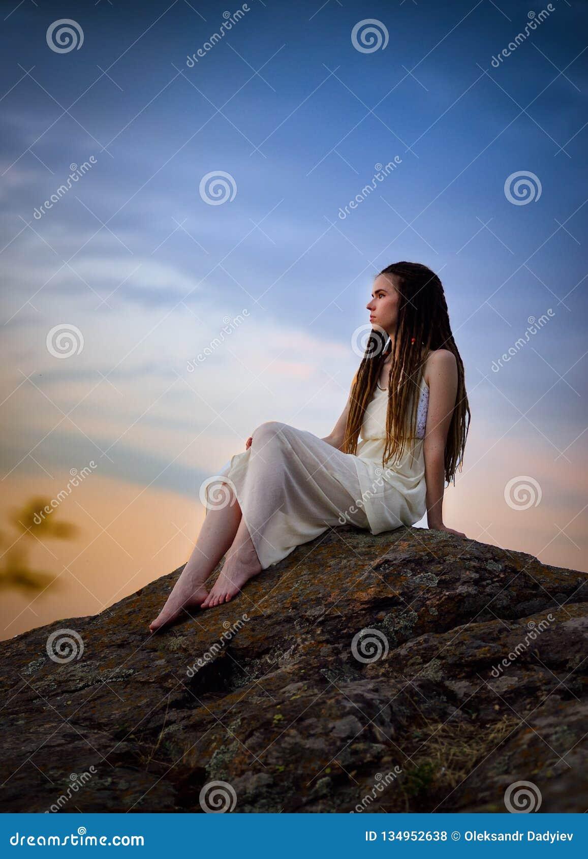 Bella ragazza stessa con i dreadlocks su una roccia in un vestito leggero