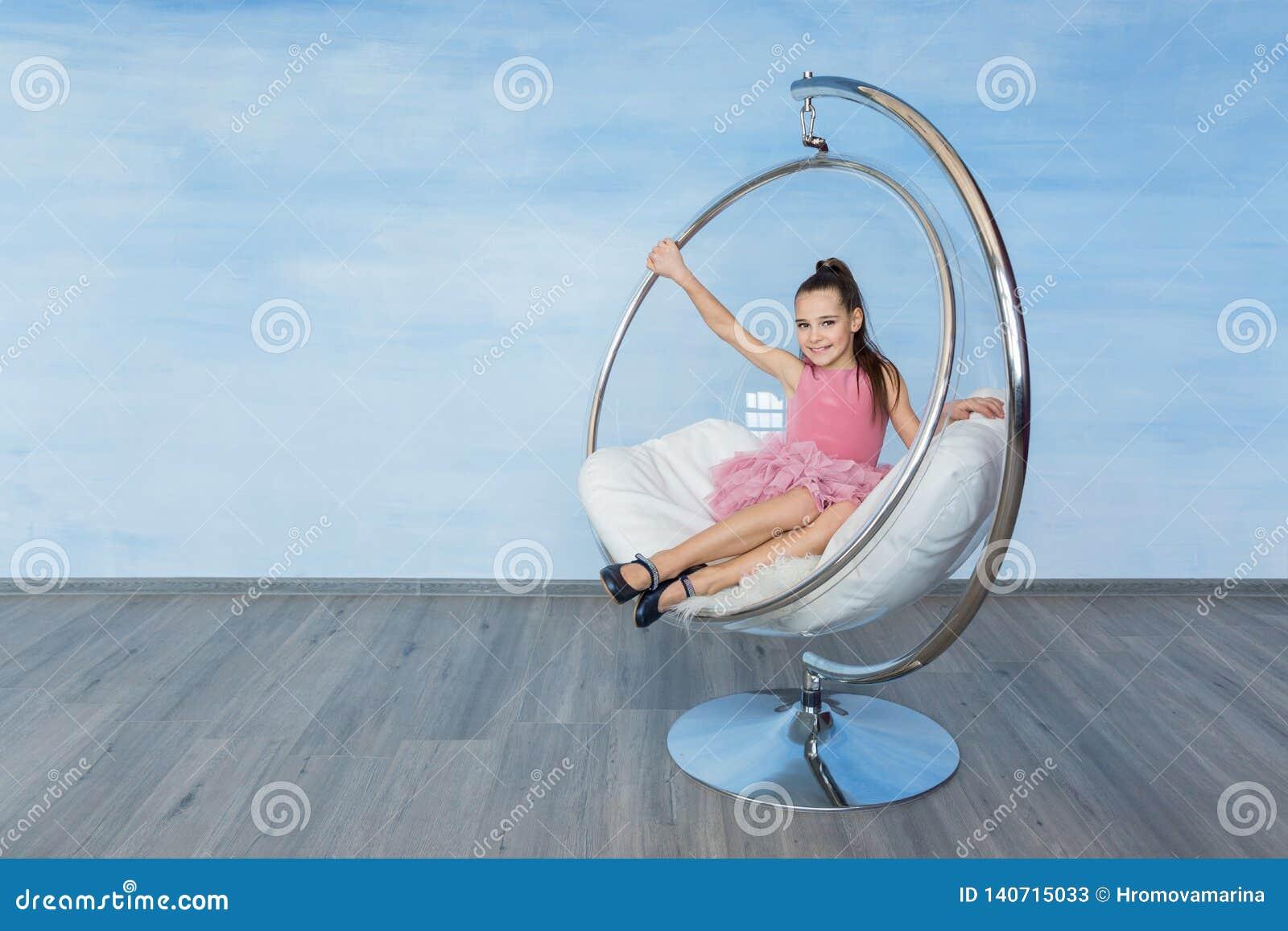 Bella ragazza teenager in un vestito rosa che si siede sulla sedia di vetro rotonda su un fondo blu
