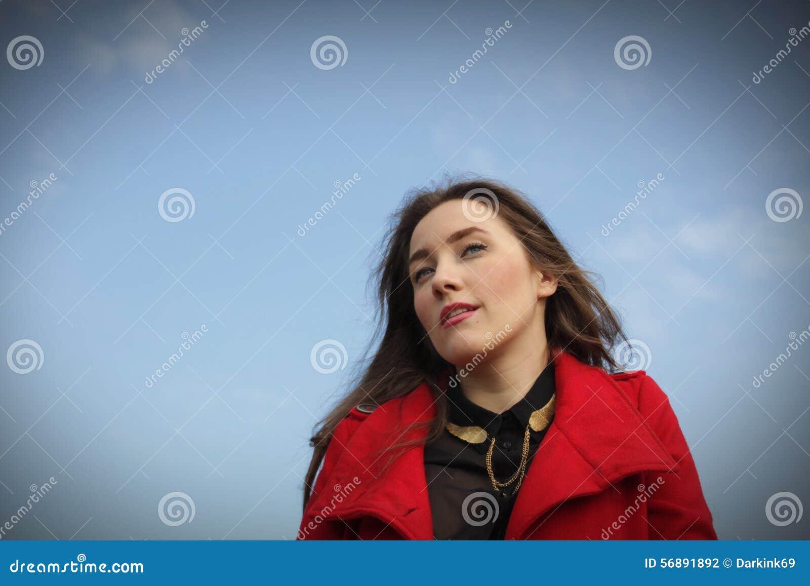 Bella ragazza in un cappotto rosso su un fondo del cielo blu