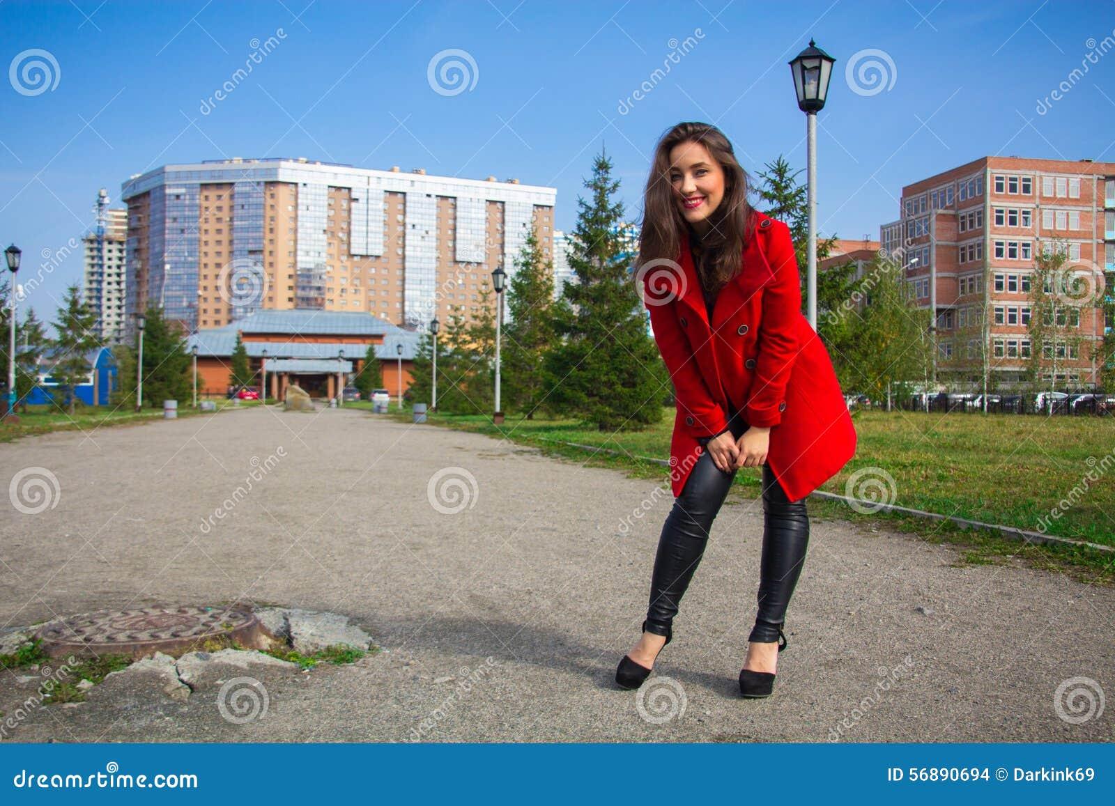 Bella ragazza in un cappotto rosso su un vicolo del parco