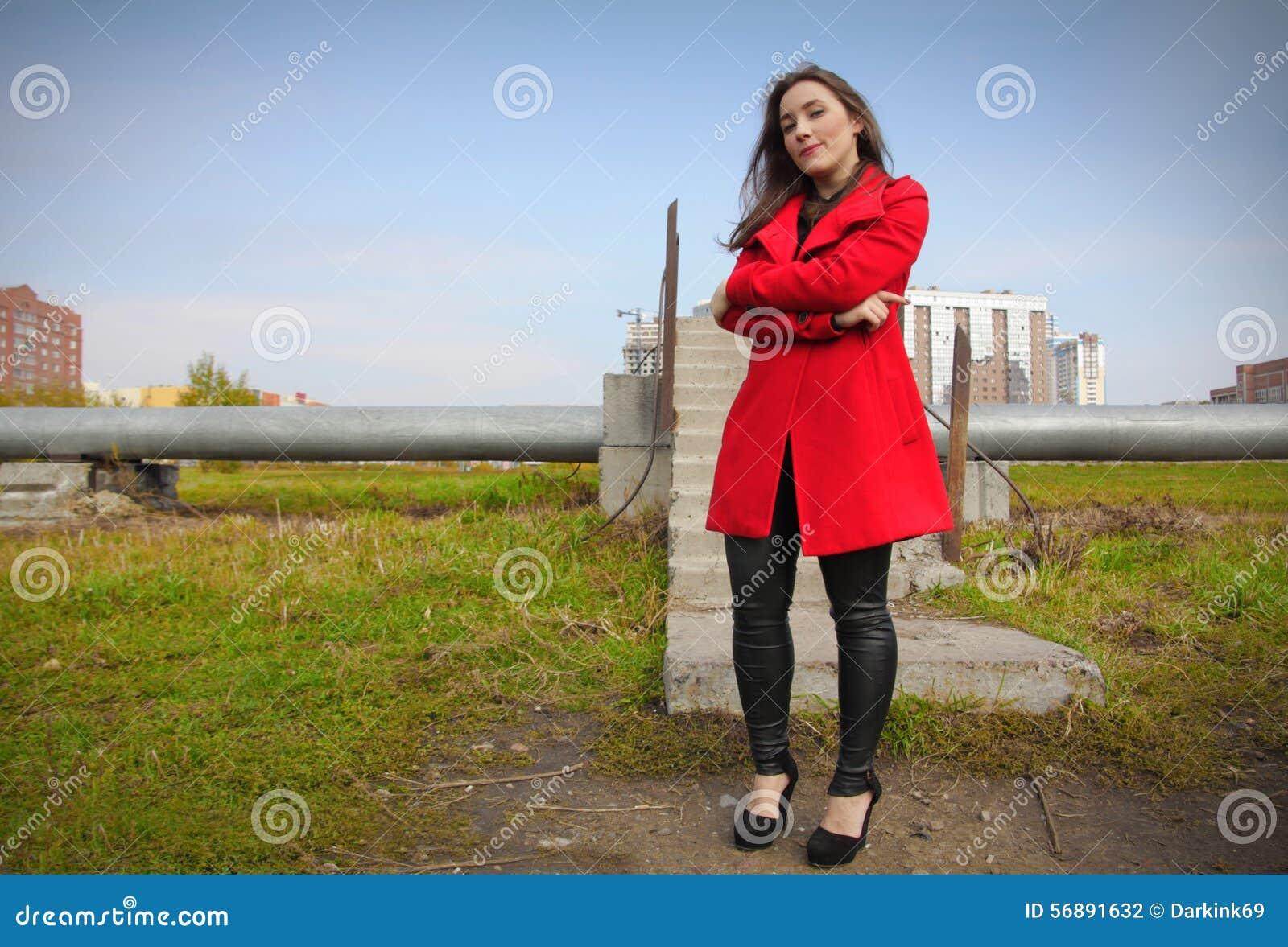 Bella ragazza in un cappotto rosso sui precedenti della conduttura