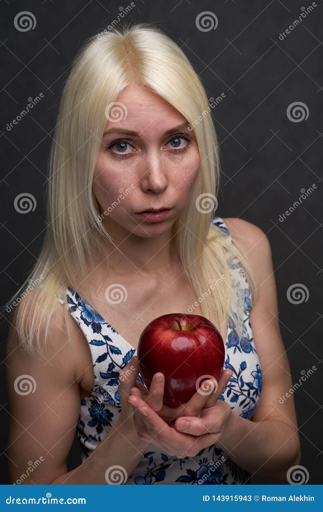 Bella ragazza in un vestito alla moda con la mela