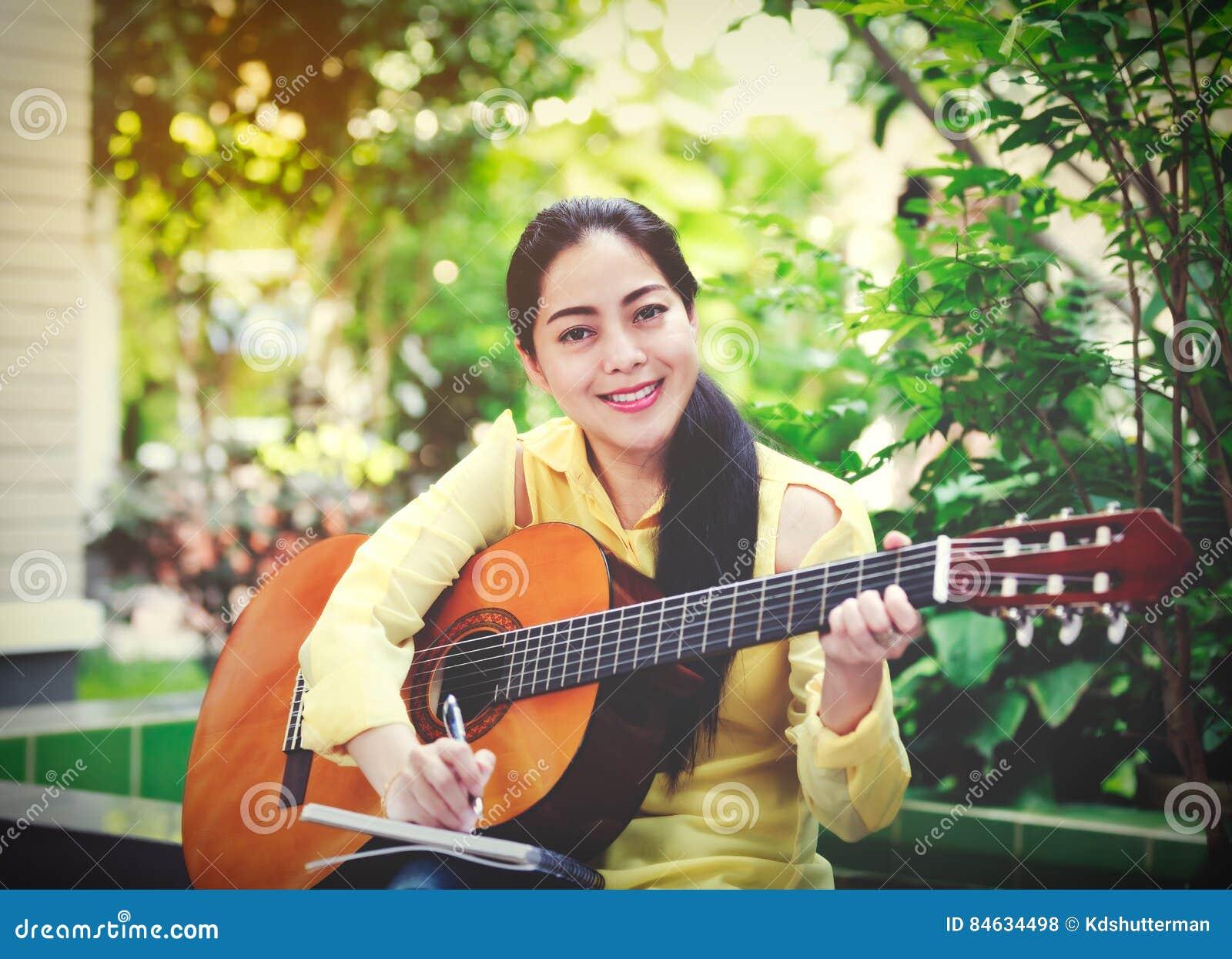 Bella scrittura del cantautore sulla carta per appunti con la chitarra acustica