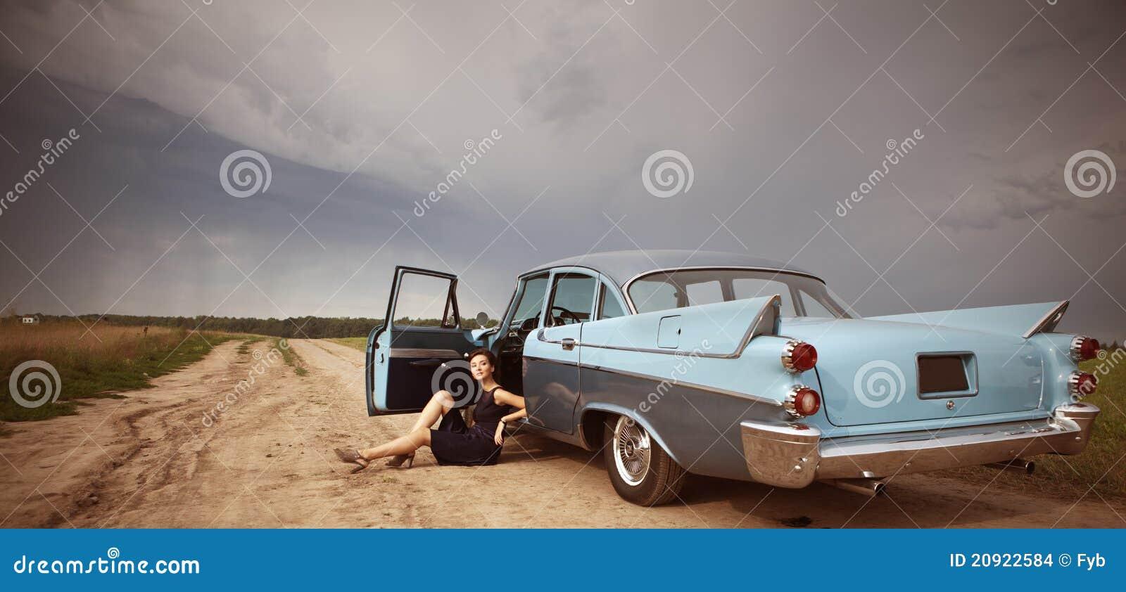 Bella signora che si leva in piedi vicino alla retro automobile