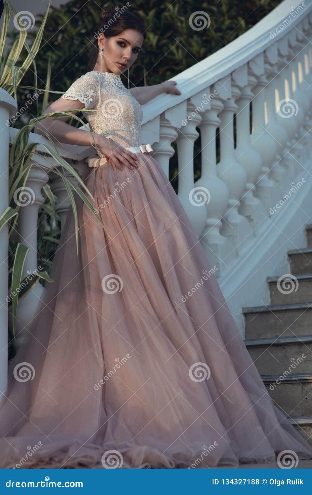 Bella signora con perfetto compone nel vestito lussuoso dalla sala da ballo con la gonna di Tulle e nella condizione superiore di