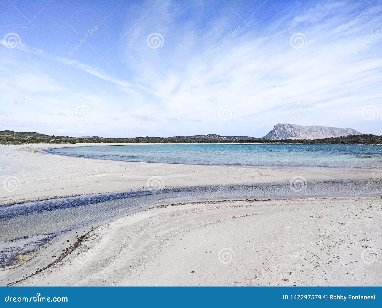 Bella spiaggia bianca abbandonata in Sardegna, LU Impostu, con il mare in varie tonalità del blu, curve della sabbia segnate da a