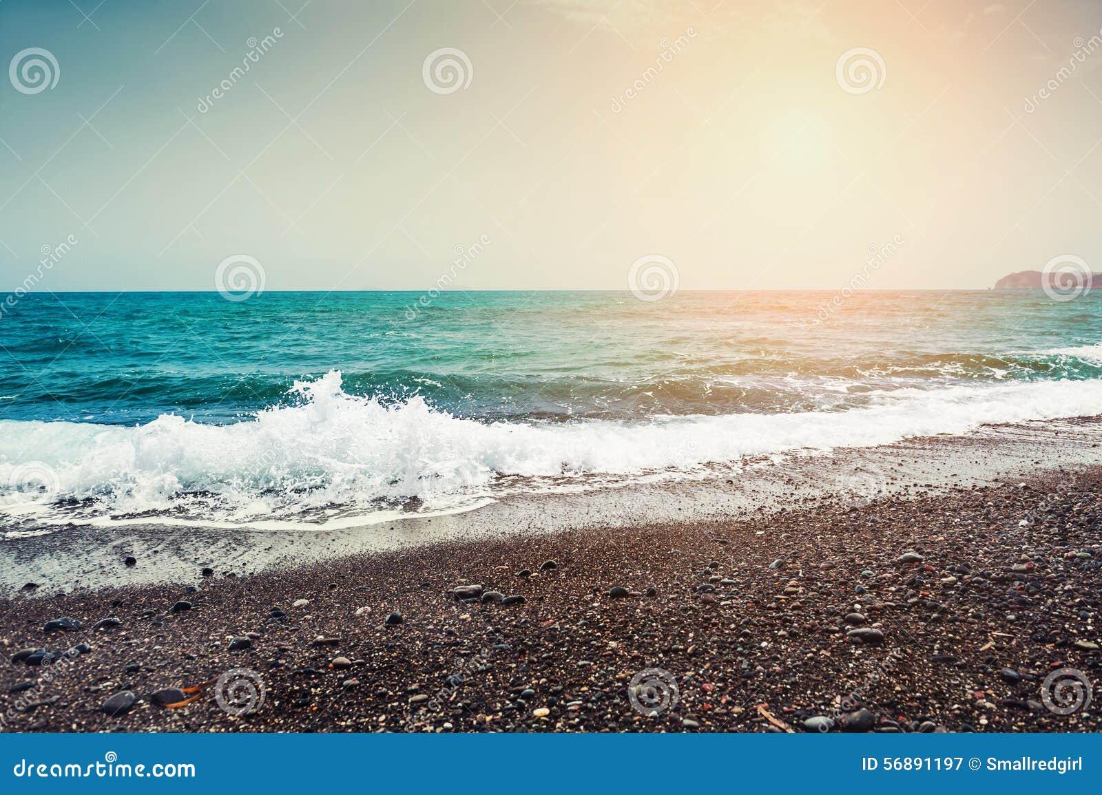 Bella spiaggia con acqua del turchese e la sabbia nera