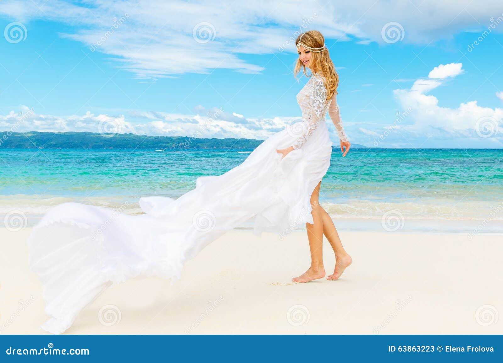 d45ab2d9ef74 Bella sposa bionda in vestito da sposa bianco con il grande treno lungo  divertendosi sul mare della riva Mare tropicale nei precedenti Concetto di  vacanze ...