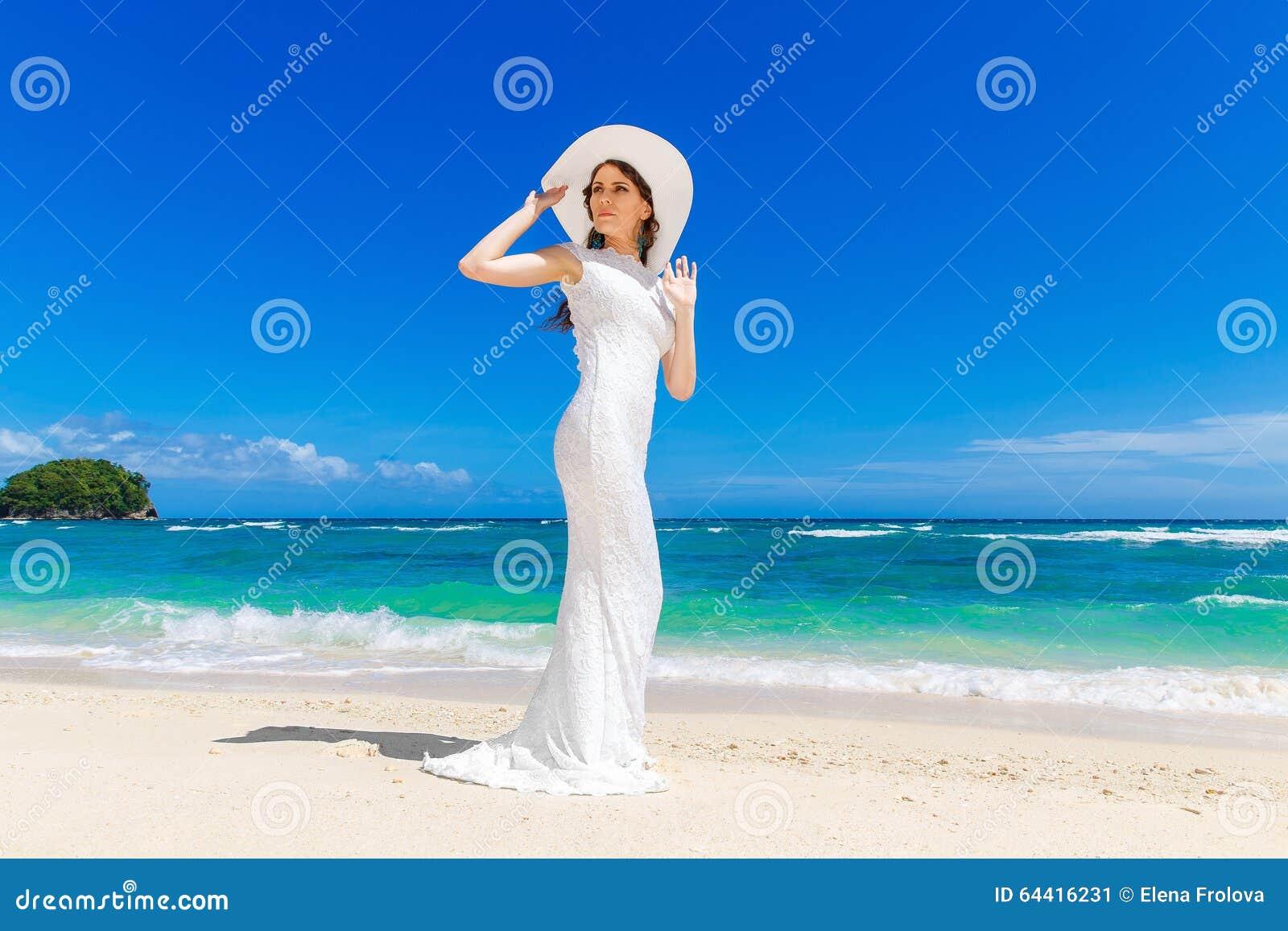 342c61722605 Bella sposa castana in cappello bianco di paglia e del vestito da sposa  divertendosi sul mare della riva Mare tropicale nei precedenti Concetto di  vacanze ...