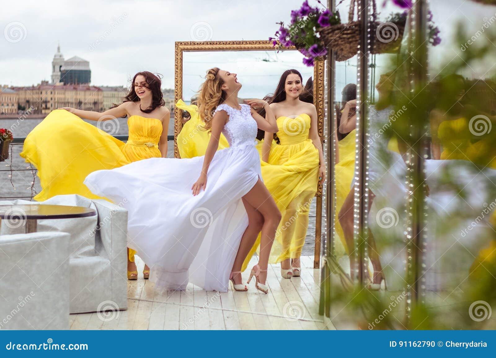 62ab997007dc Bella sposa e due damigelle d onore insieme su un terrazzo di estate un  ristorante del