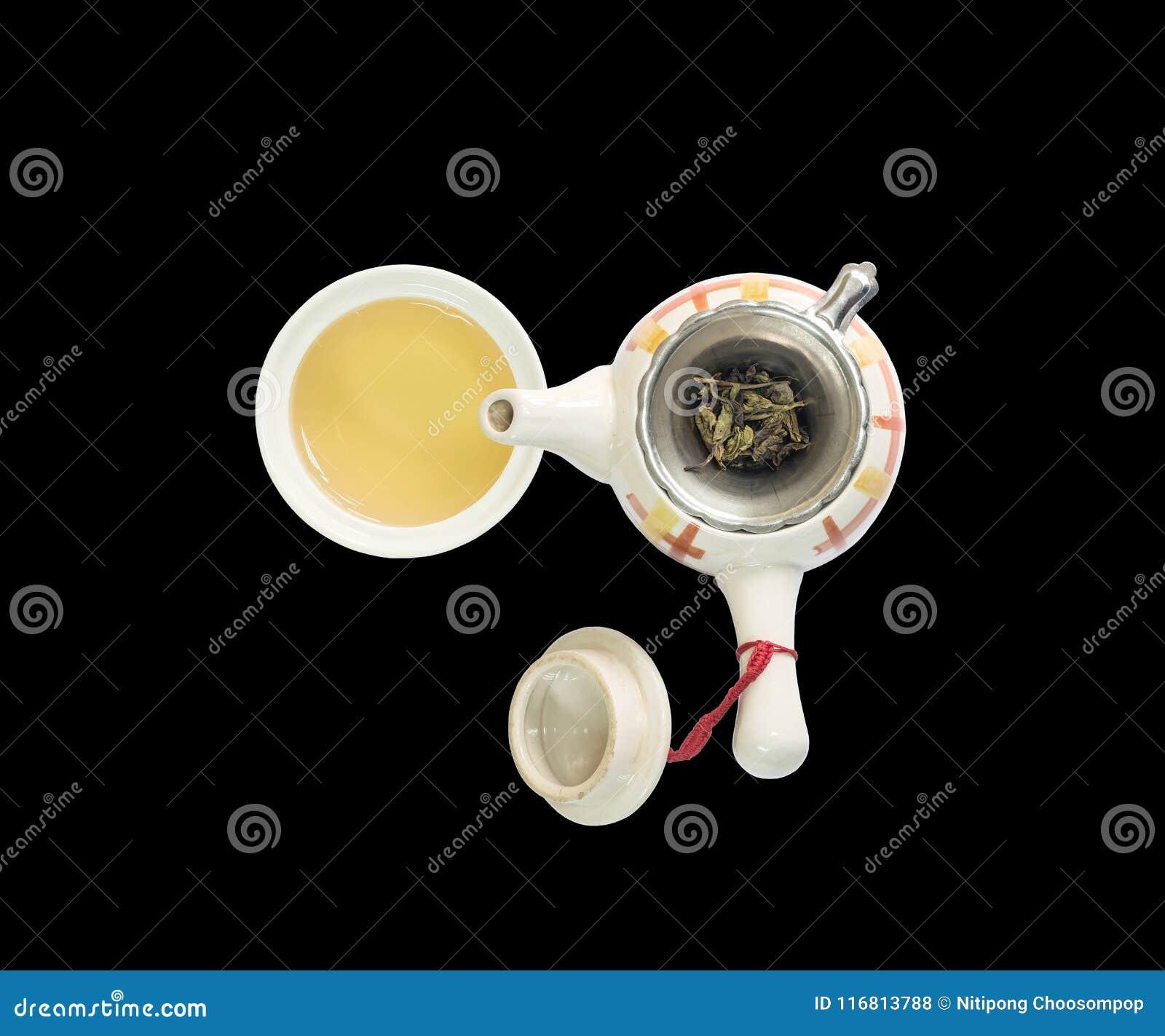 Bella teiera ceramica del primo piano con le foglie di tè secche sul filtro del tè e sul tè marrone in una tazza di tè isolata su