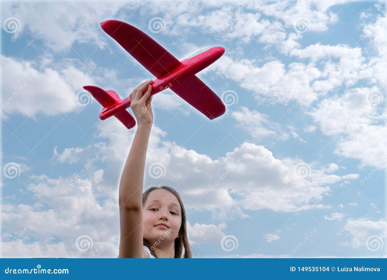 Bella tenuta del bambino in mani un aeroplano rosso del giocattolo su un fondo di cielo blu