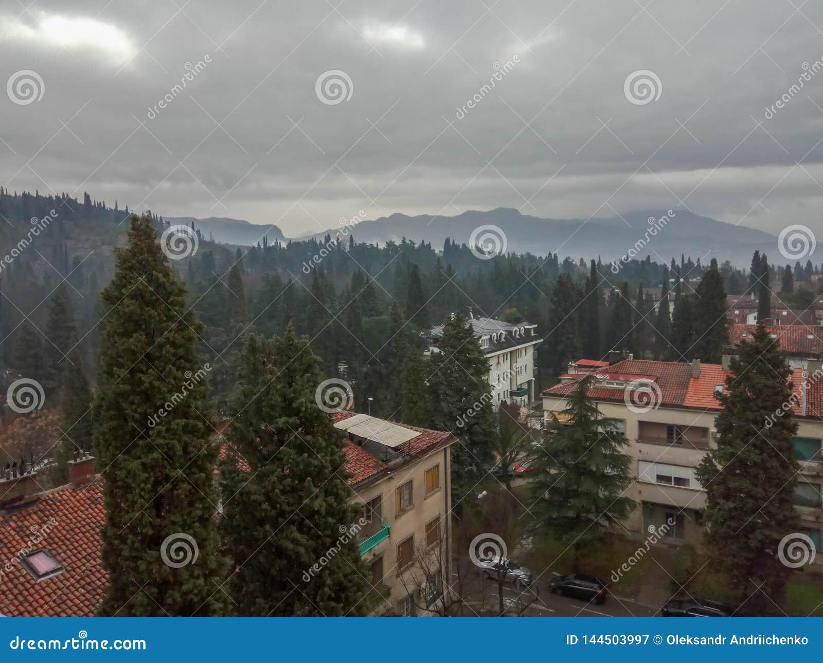 Bella vista della città al piede delle montagne nebbiose verdi contro il cielo nuvoloso