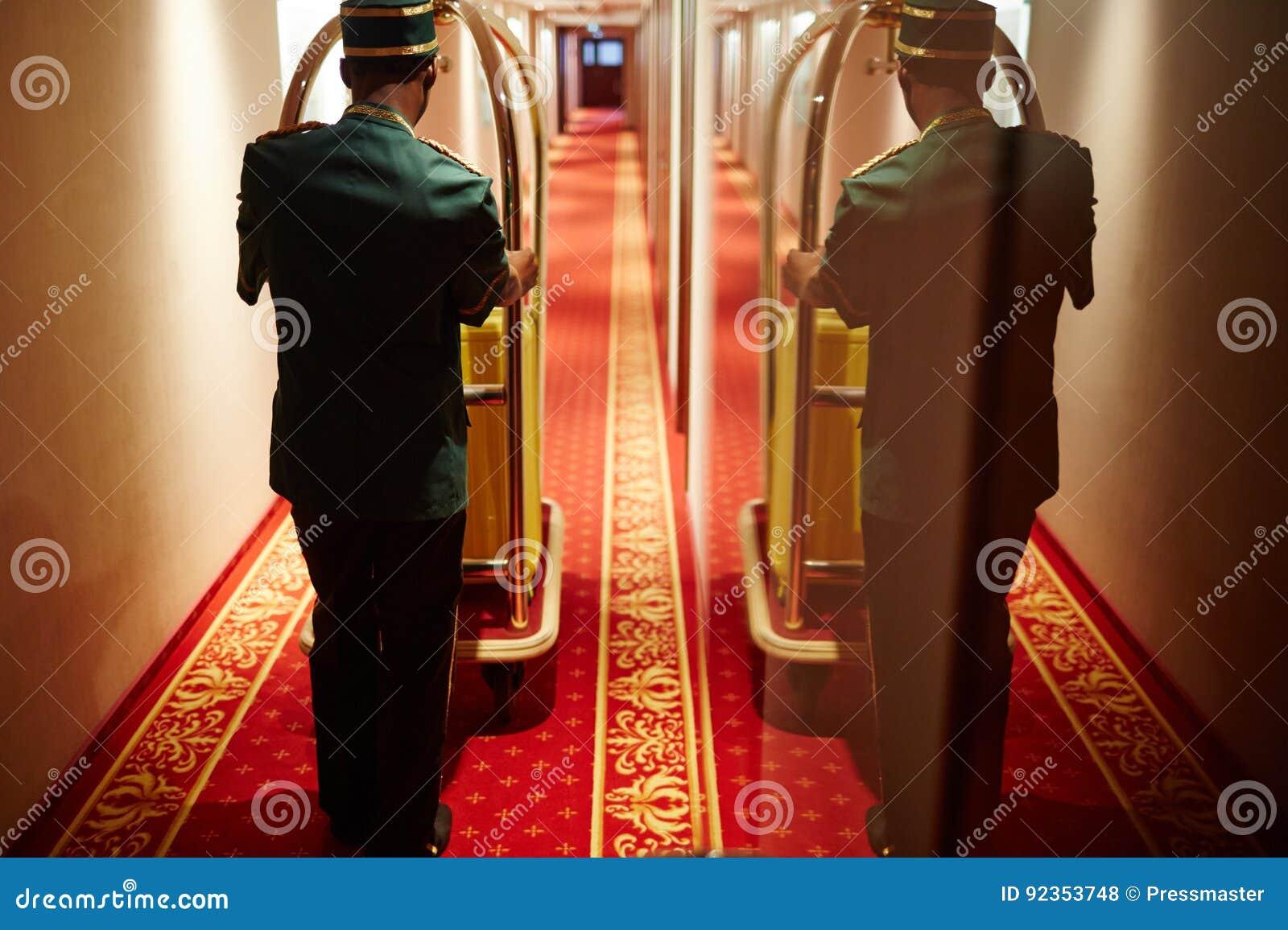 Bellboy dosunięcia bagażu fura w Hotelowym korytarzu