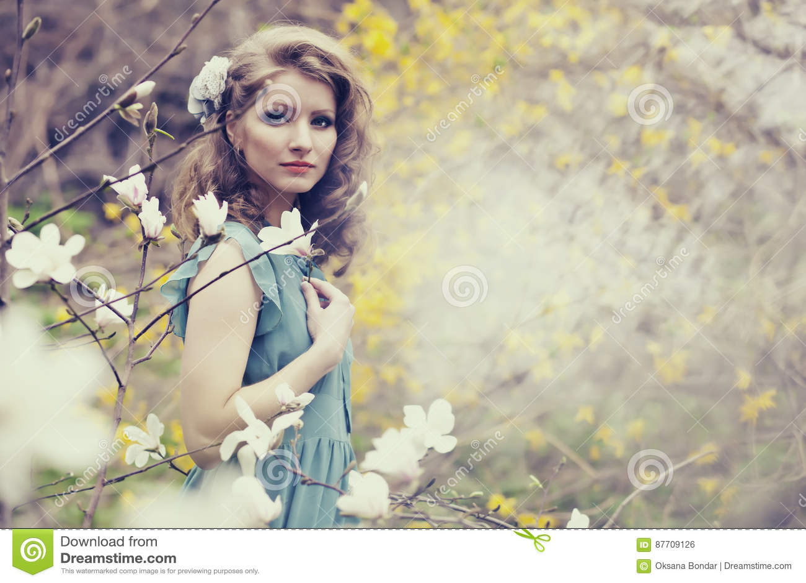 Belle blonde avec la belle coiffure dans la robe bleue de vintage dans une magnolia luxuriante de jardin de ressort