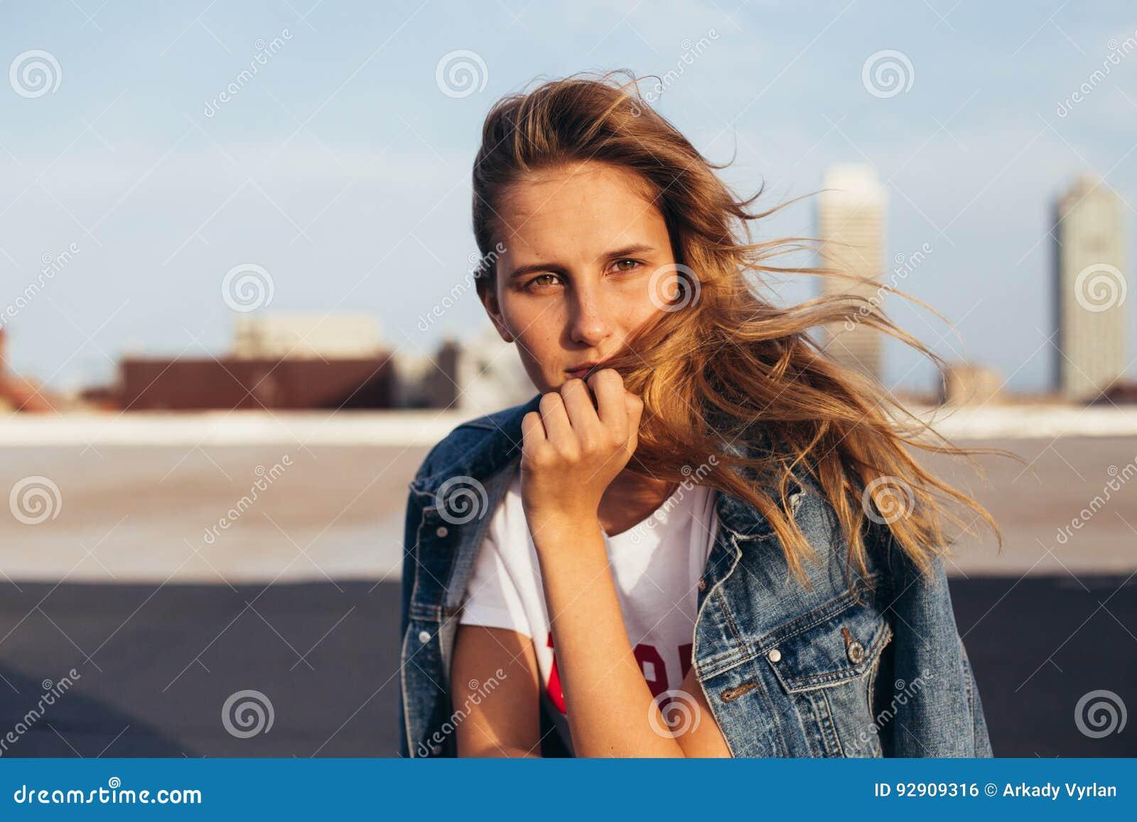 Belle blonde dans la veste de denim avec la planche à roulettes