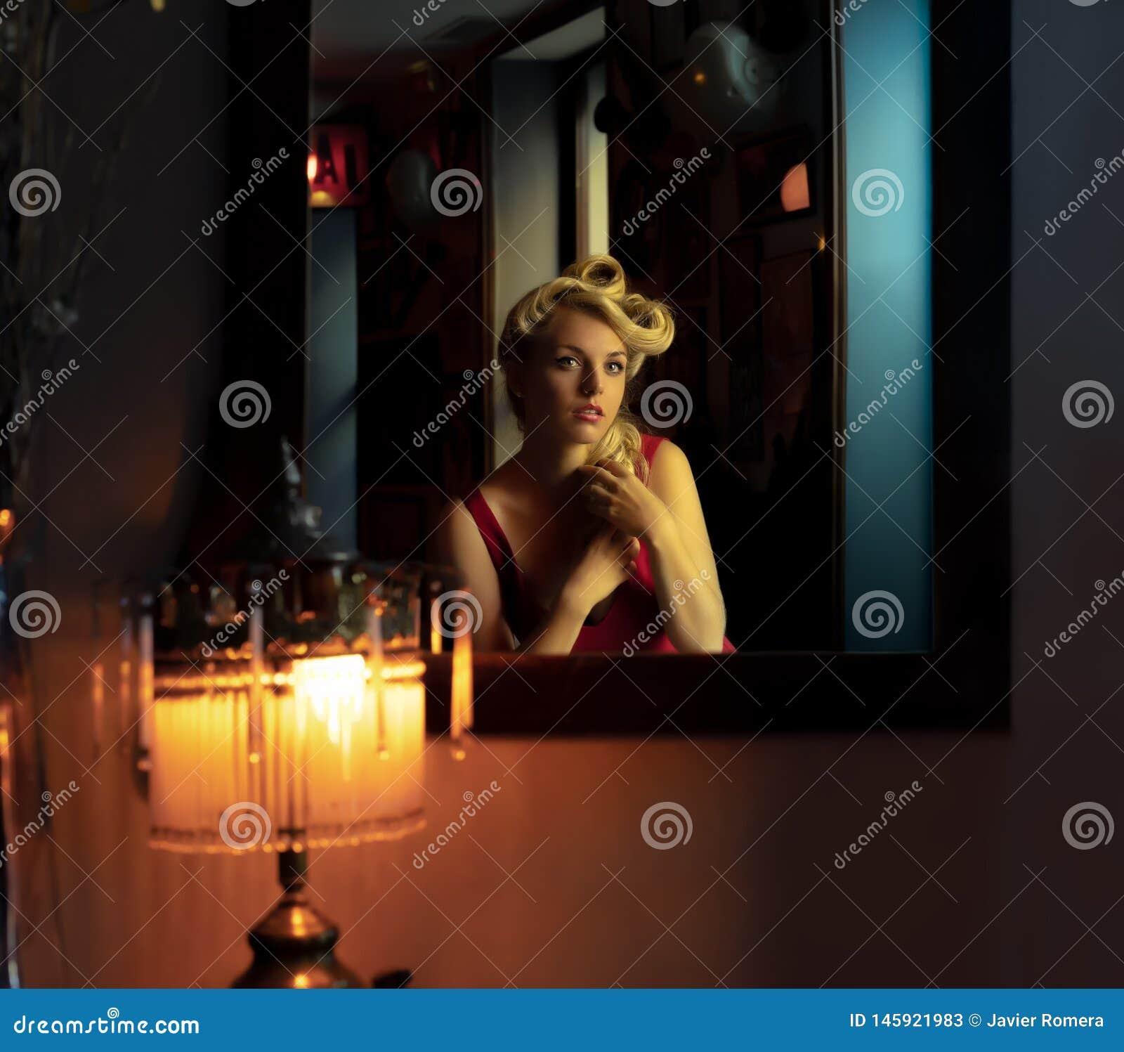 Belle blonde regardant elle-même dans un miroir