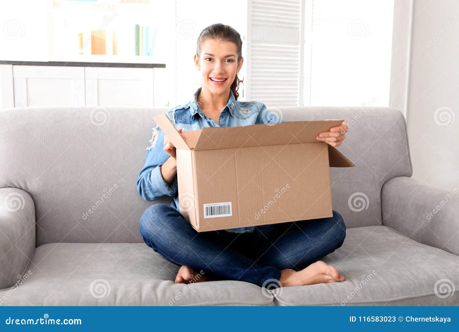 Belle boîte d ouverture de jeune femme avec le colis