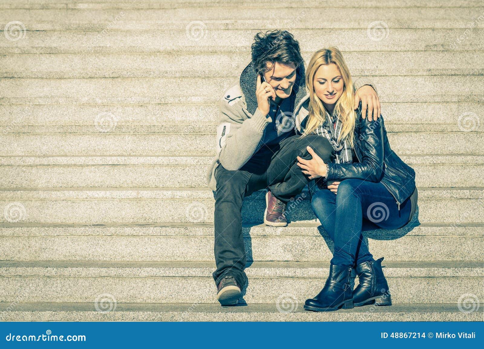 Belle coppie dei pantaloni a vita bassa nell amore che ha una chiamata dello smartphone