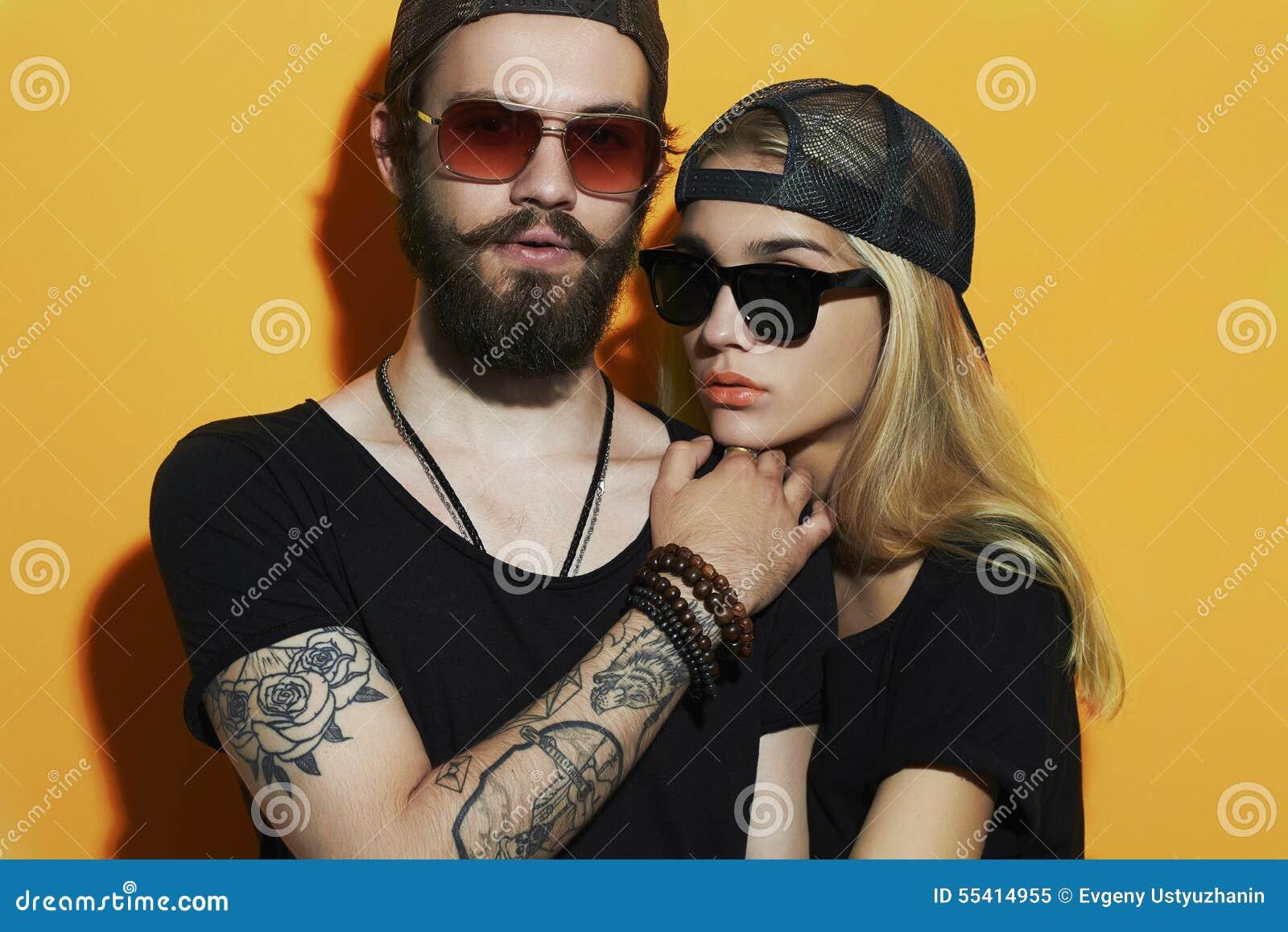 Belle coppie di modo insieme Ragazzo e ragazza dei pantaloni a vita bassa del tatuaggio