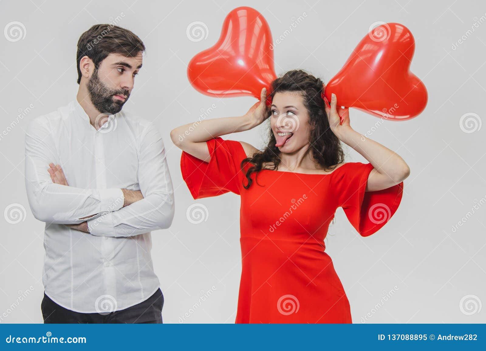 Belle coppie romantiche isolate su fondo bianco Una giovane donna attraente tiene i palloni sopra la sua testa, sua