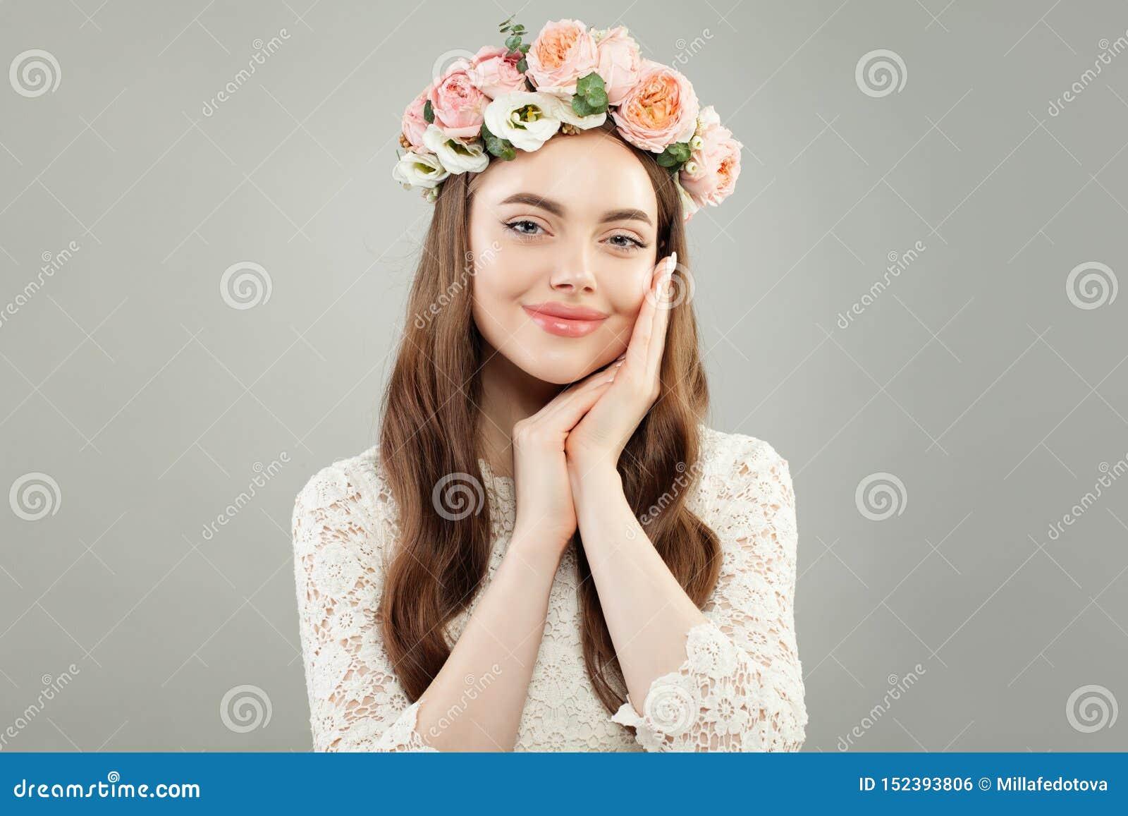 Belle détente de sourire de femme Joli visage modèle avec la peau claire, la longue coiffure bouclée et les fleurs