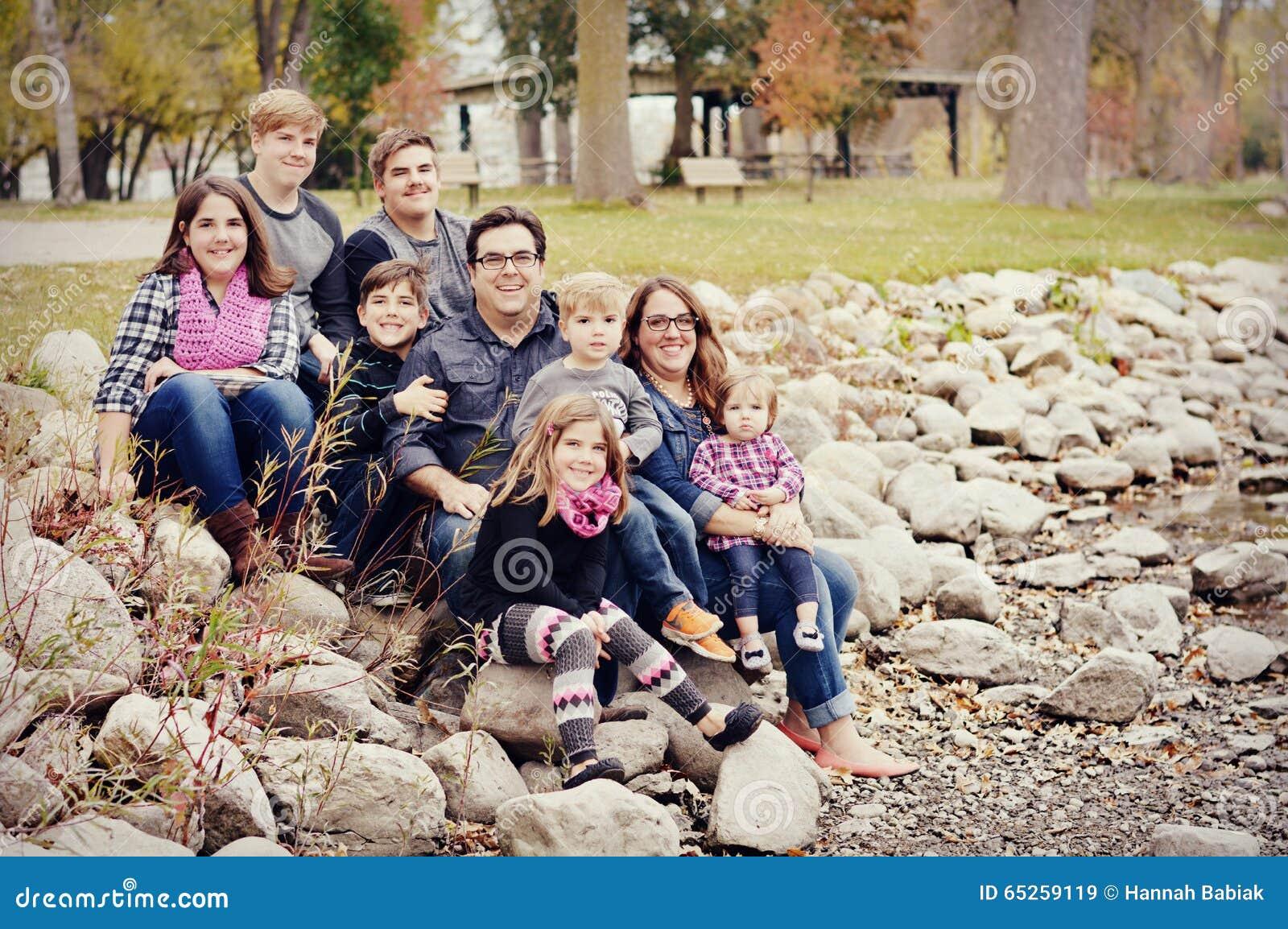 Belle famille nombreuse s asseyant sur des roches