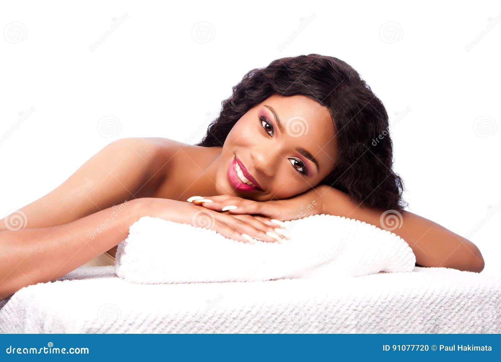 Belle femme à la station thermale s étendant sur des serviettes
